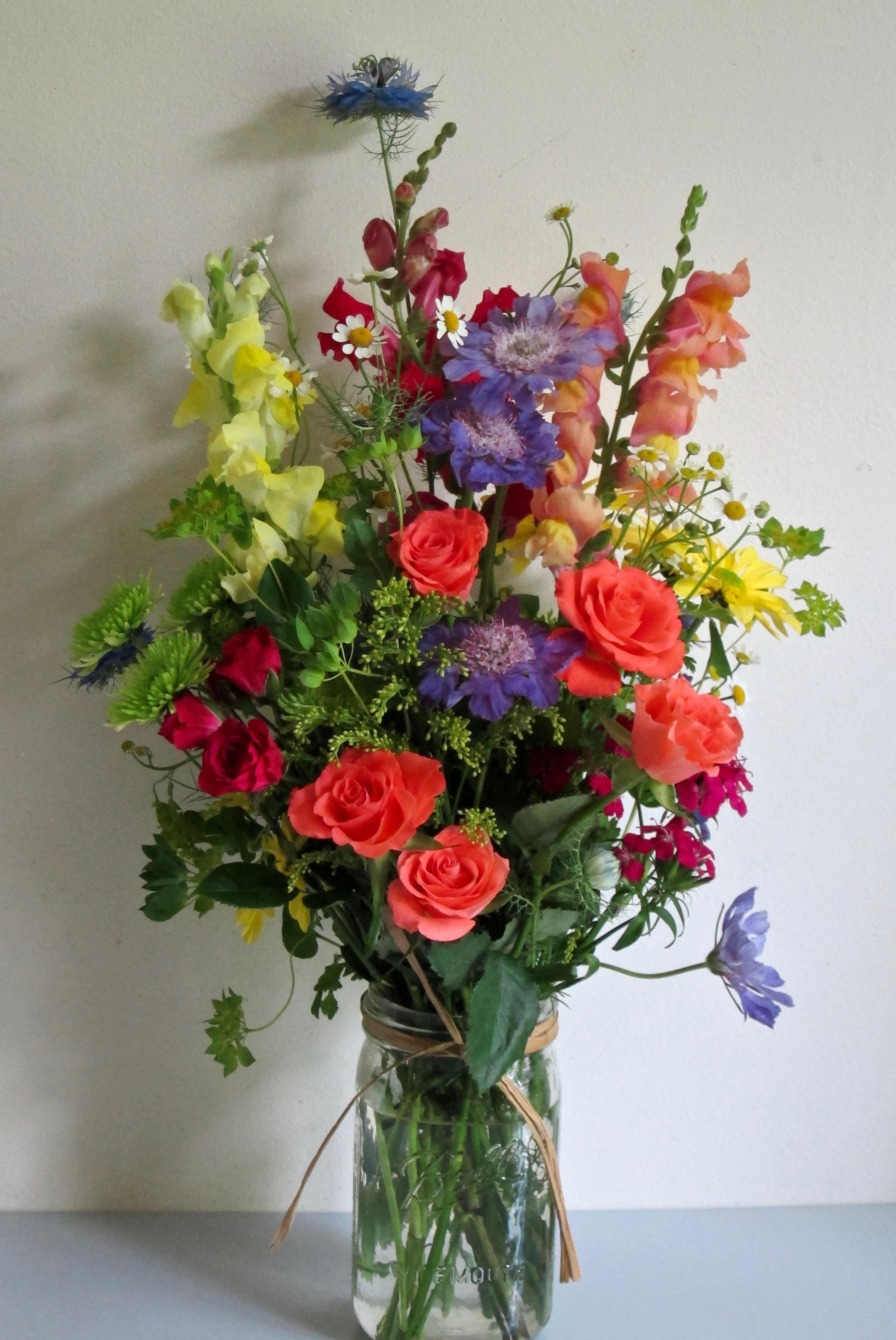 CASUAL COUNTRY MASON JAR   of colorful seasonal picks, raffia ribbon, $40.