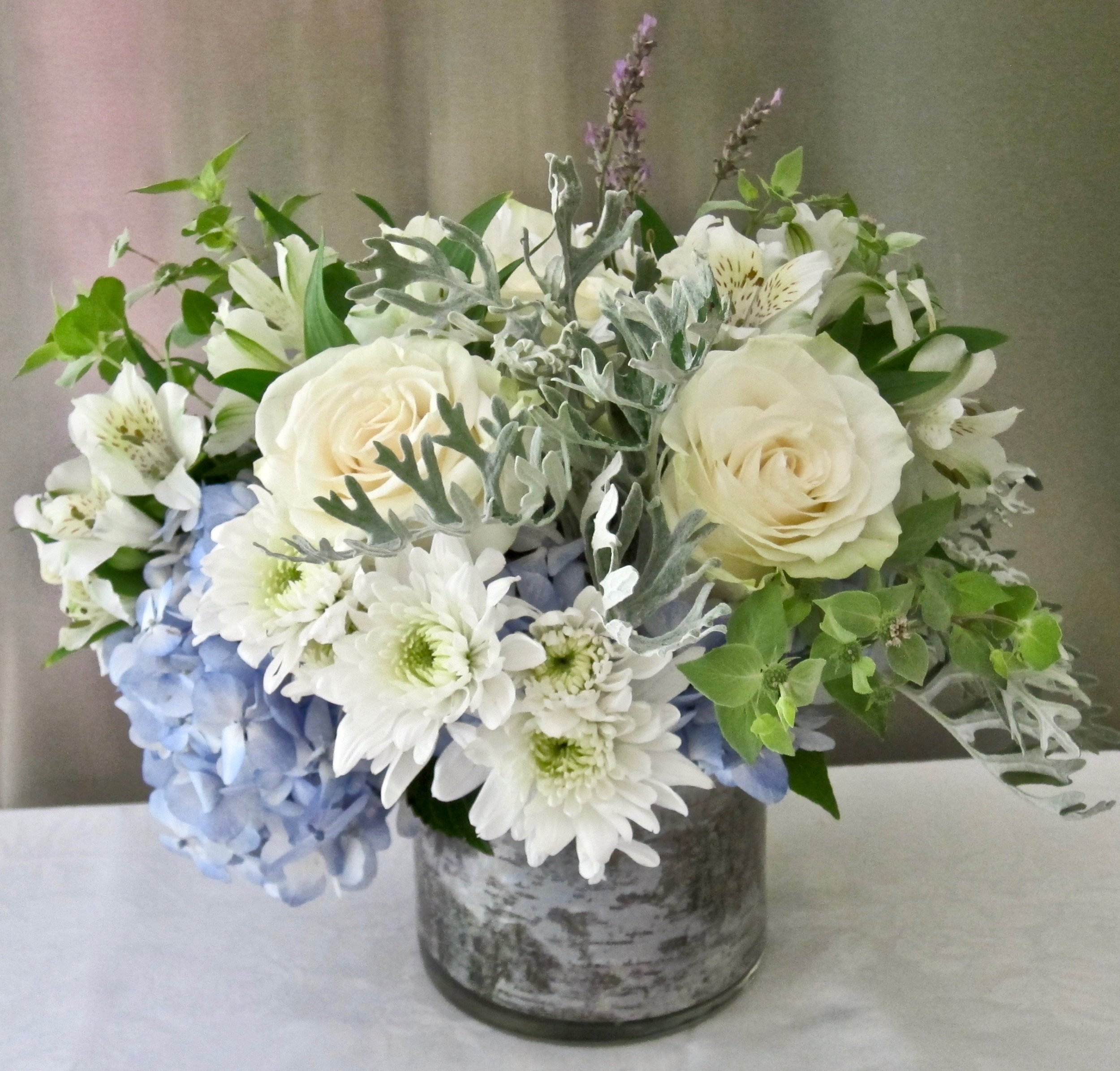 TABLETOP CENTERPIECE  White roses, mums, alstroemeria in a bed of blue or green hydrangeas, 10 inches high and wide, $75.