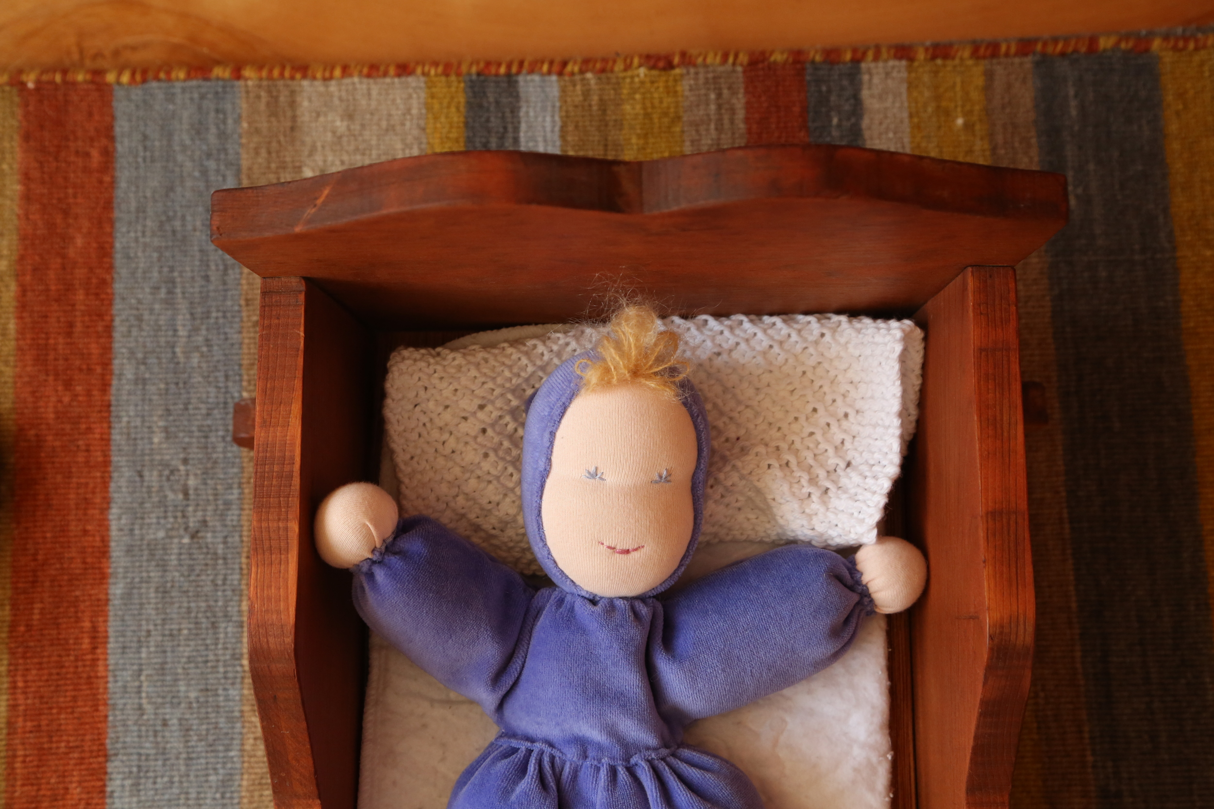 """""""Dolly is go night-night.""""  This is the doll I made G for Christmas.  She's sleeping on a washcloth made by my talented friend Sarah, who kindly sent me a resuscitation package in late winter containing desert-related things I missed. (Ahhh.)  The bed I rescued from a junk yard, repaired, and stained to match the book crates."""