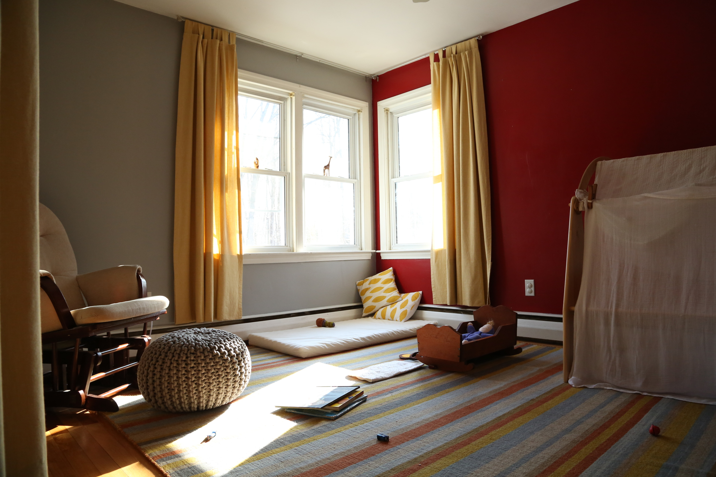 Here's an overview of the playroom as it is now.  We're going to paint the red wall grey soon.  I've tried various arrangements of the furniture and materials but always find the children shy away from the red.