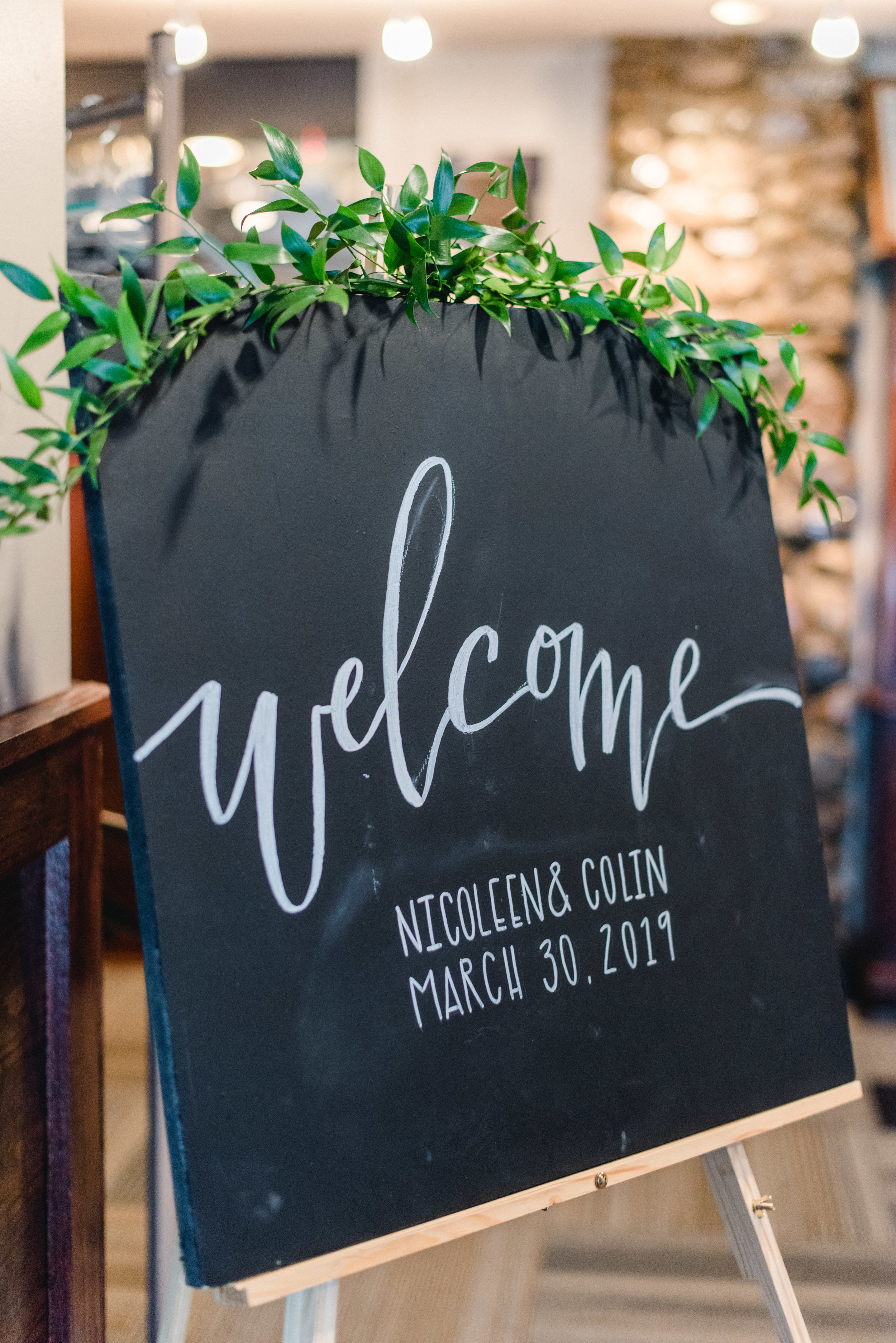 welcome sign with greenery ruscus.jpg