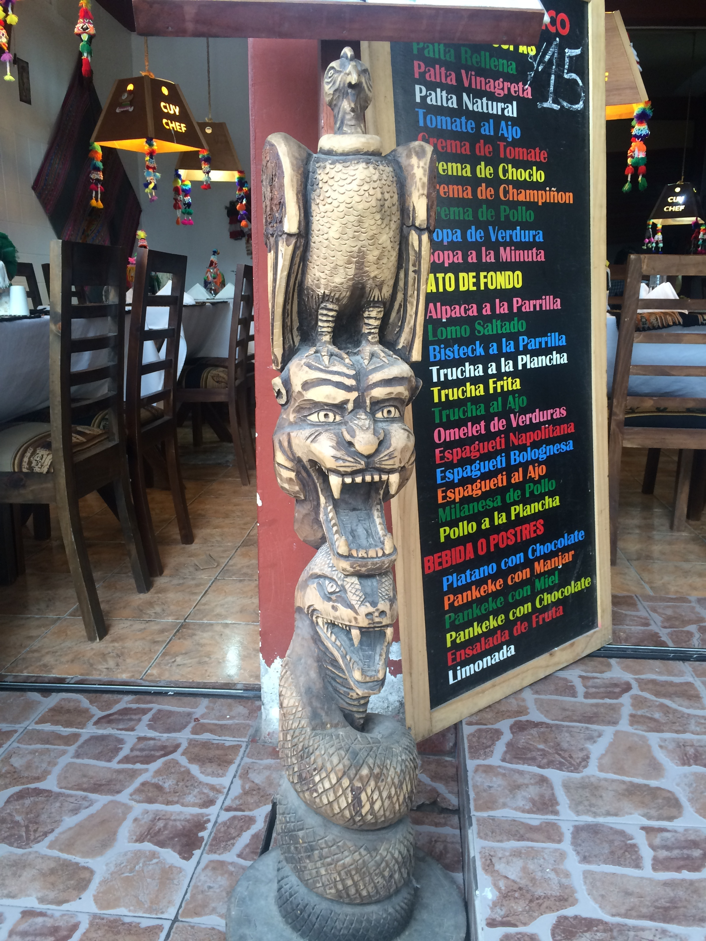 A typical tourist menu behind the ever present Incan statue representing the three levels of life. The snake (our movement through life), puma (strength), and the condor (flight and freedom).