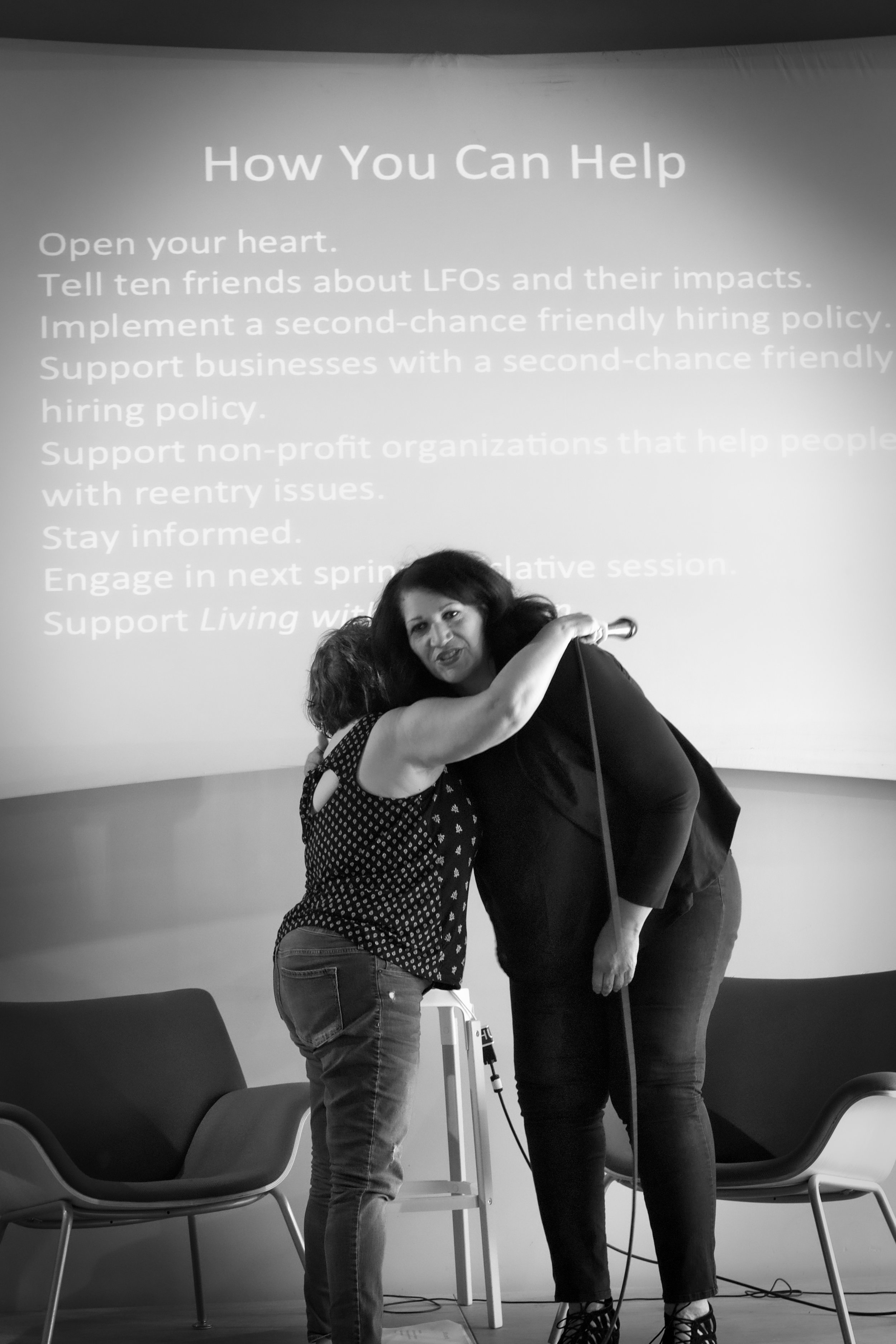 Deborah Espinosa hugging and thanking Carmen Pacheco-Jones at the artist talk at the Impact Hub, Seattle. Photo courtesy of Constance Brinkley.