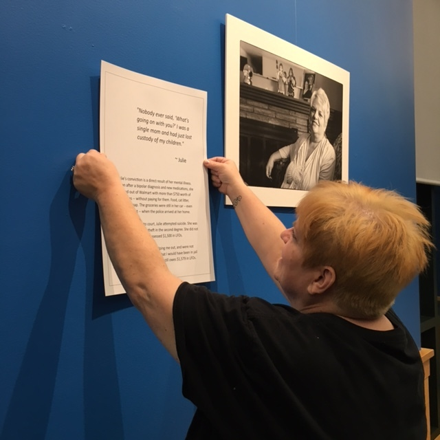 Living with Conviction  participant Julie Kelly helps hang her portrait and quote at the Spokane Public Library in January 2018.
