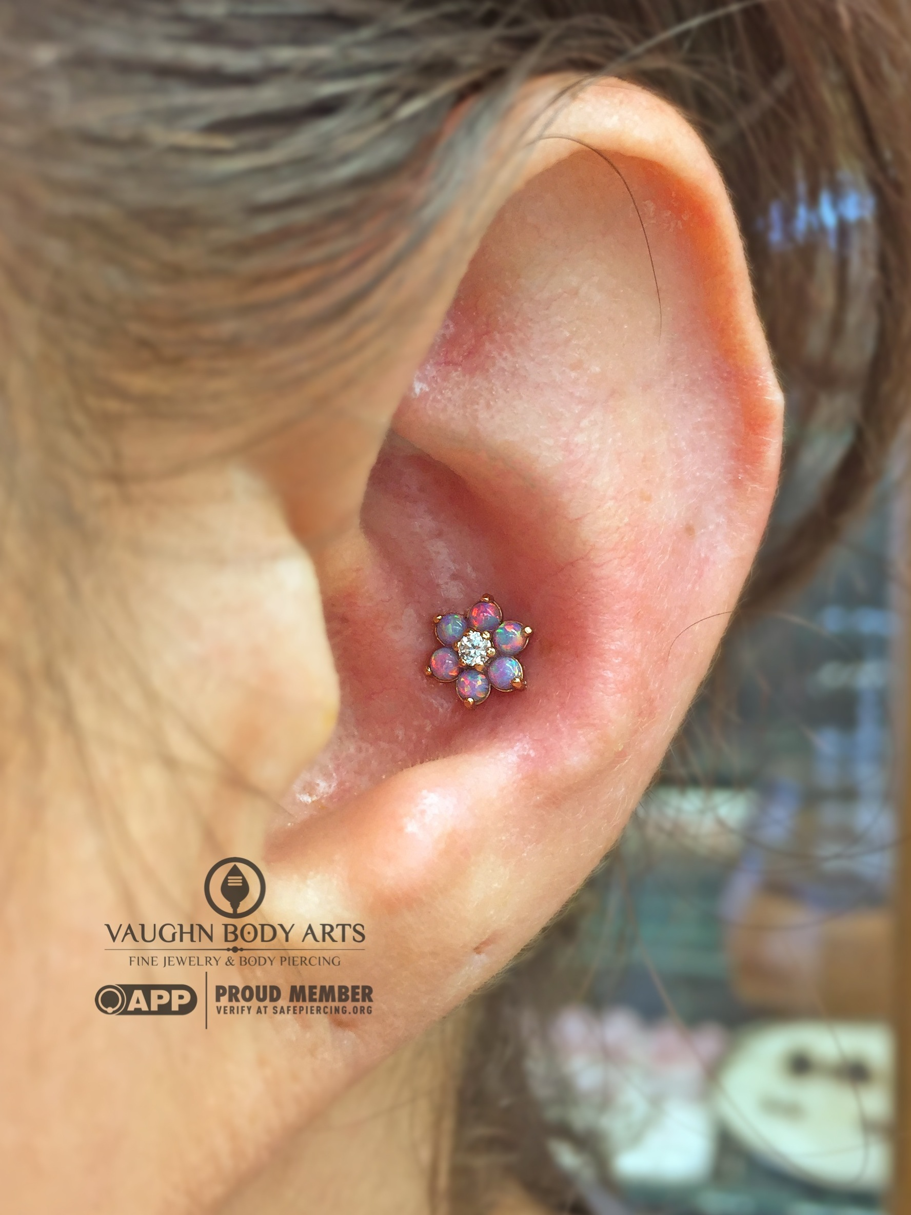 Conch piercing featuring an 18k rose gold flower from Anatometal.