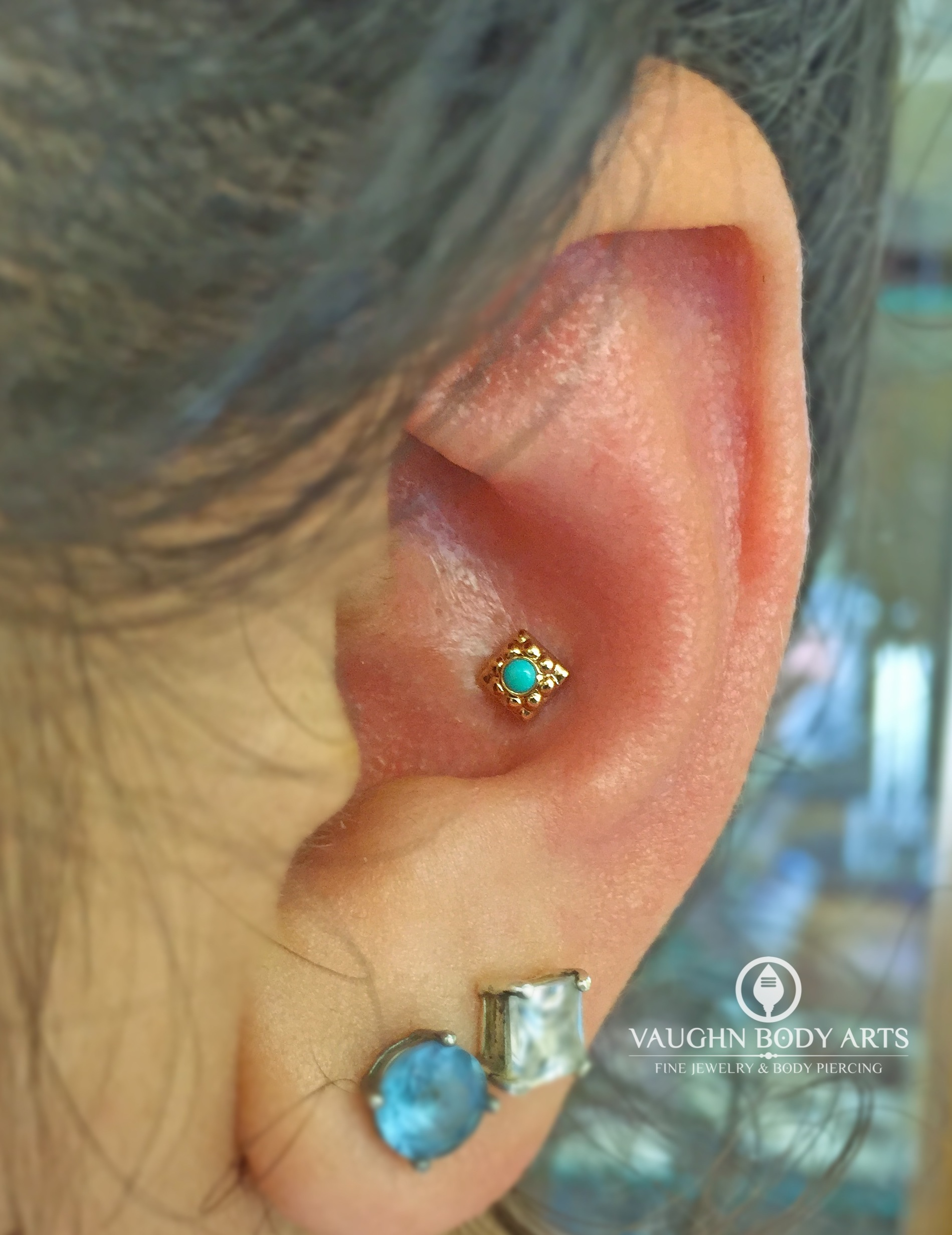"""Conch piercing with an 18k yellow gold and turquoise """"Kira"""" end from Anatometal."""