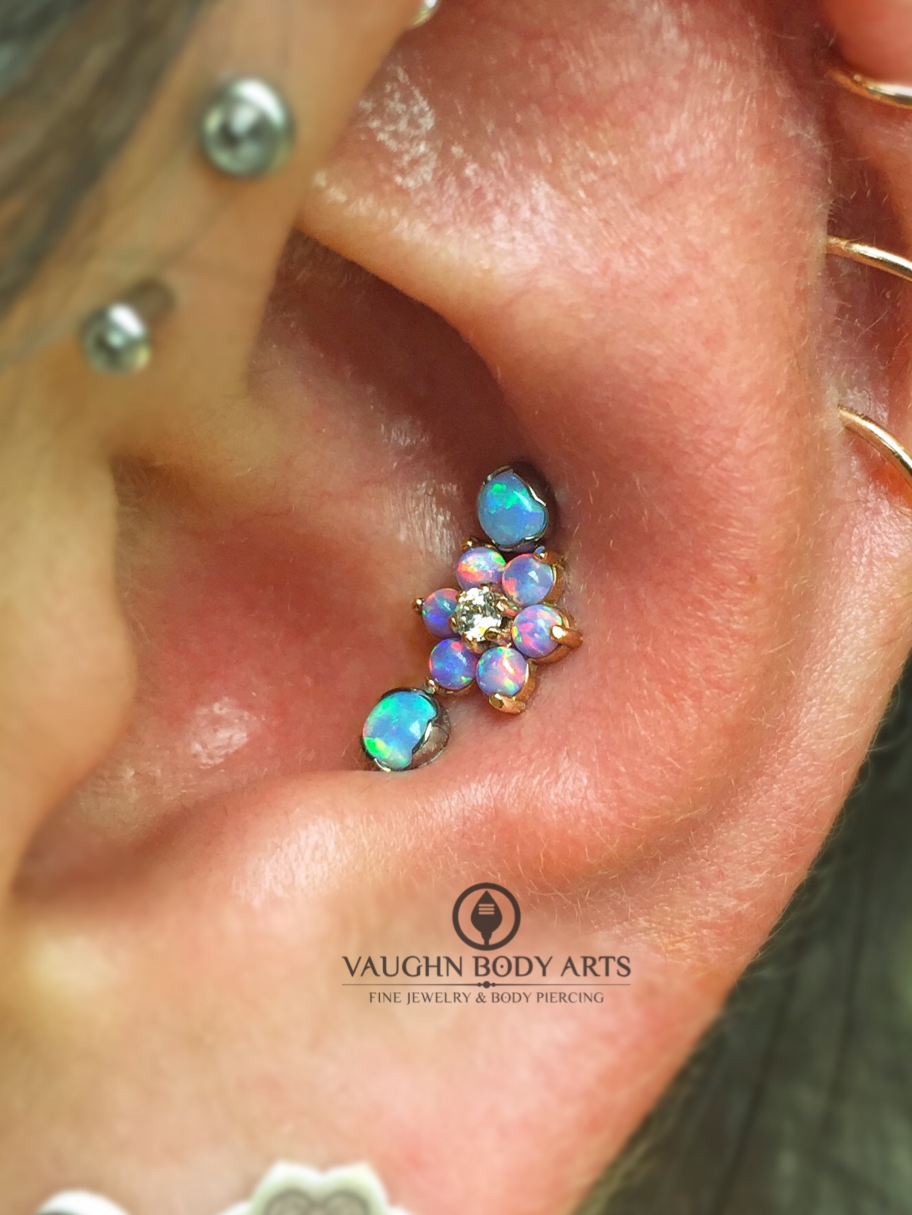 Triple conch piercing featuring jewelry from Anatometal. In the center is an 18k rose gold flower with light purple opals, and two 3mm light blue opals set in implant grade titanium.