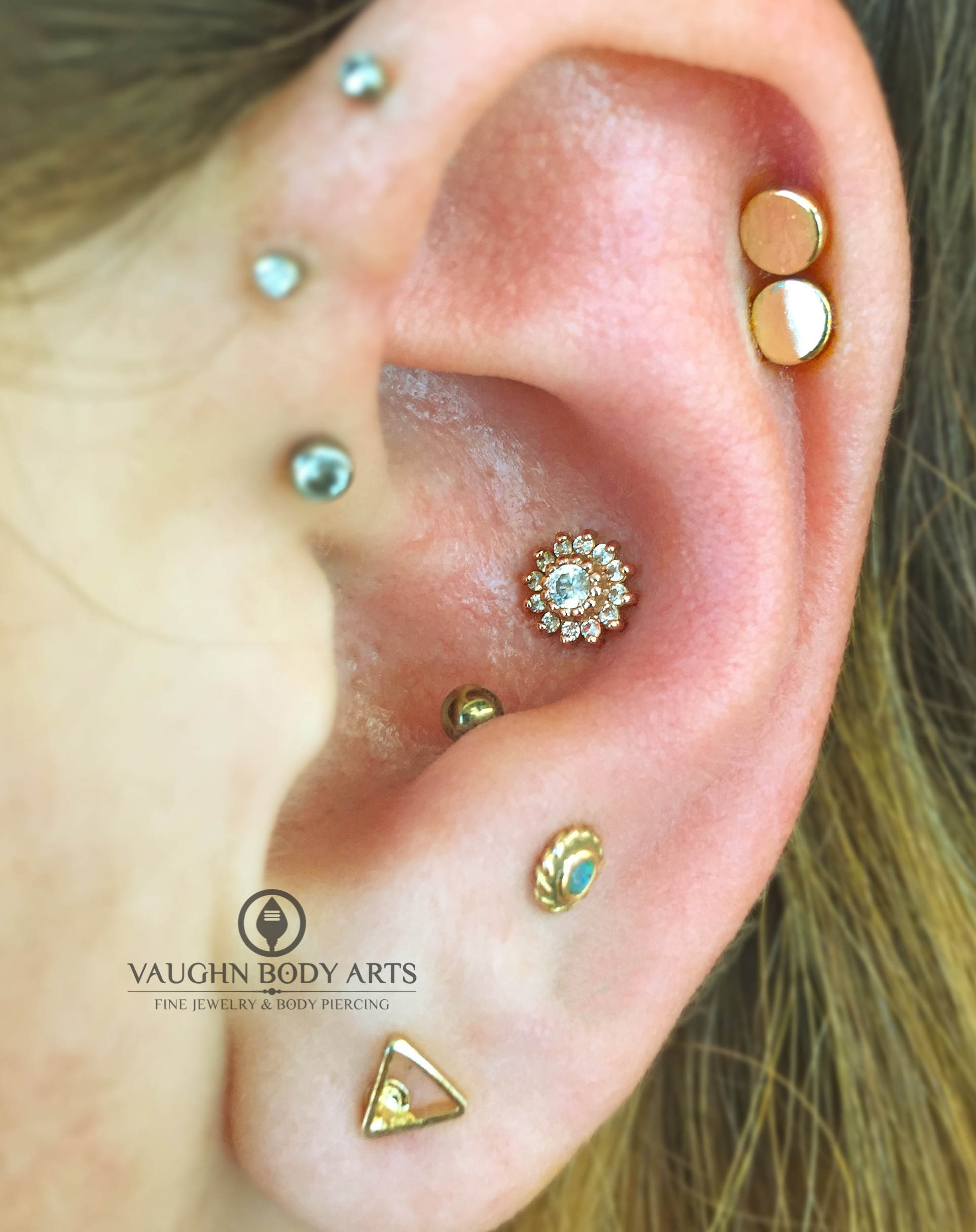 """Conch piercing with a 14k yellow gold """"Rose"""" end featuring clear cz's from BVLA."""
