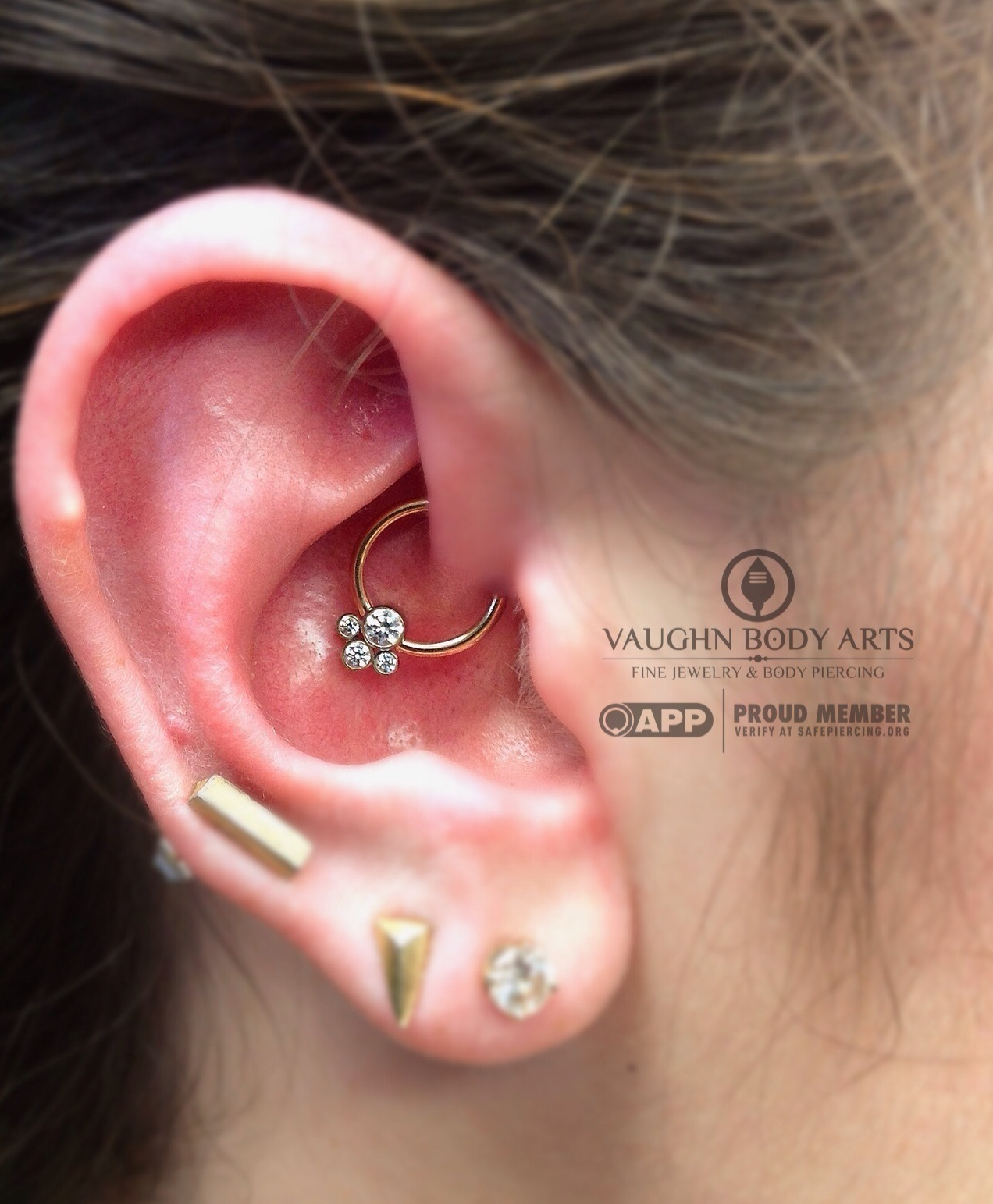 Daith piercing with a 14k yellow gold captive bead ring from BVLA holding a titanium gem cluster from Anatometal.