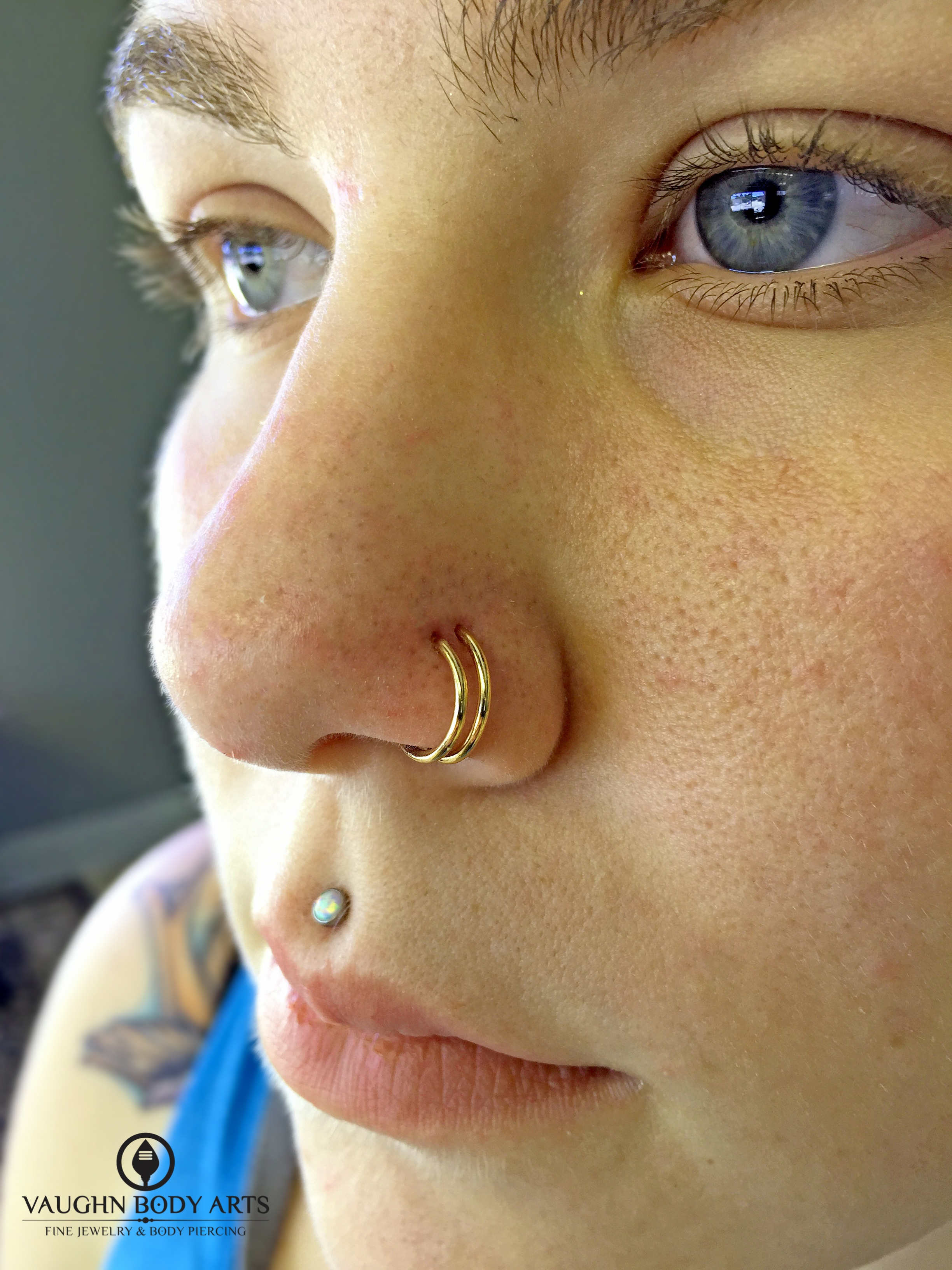 Double nostril piercings with 18k rose gold continuous rings from Anatometal.
