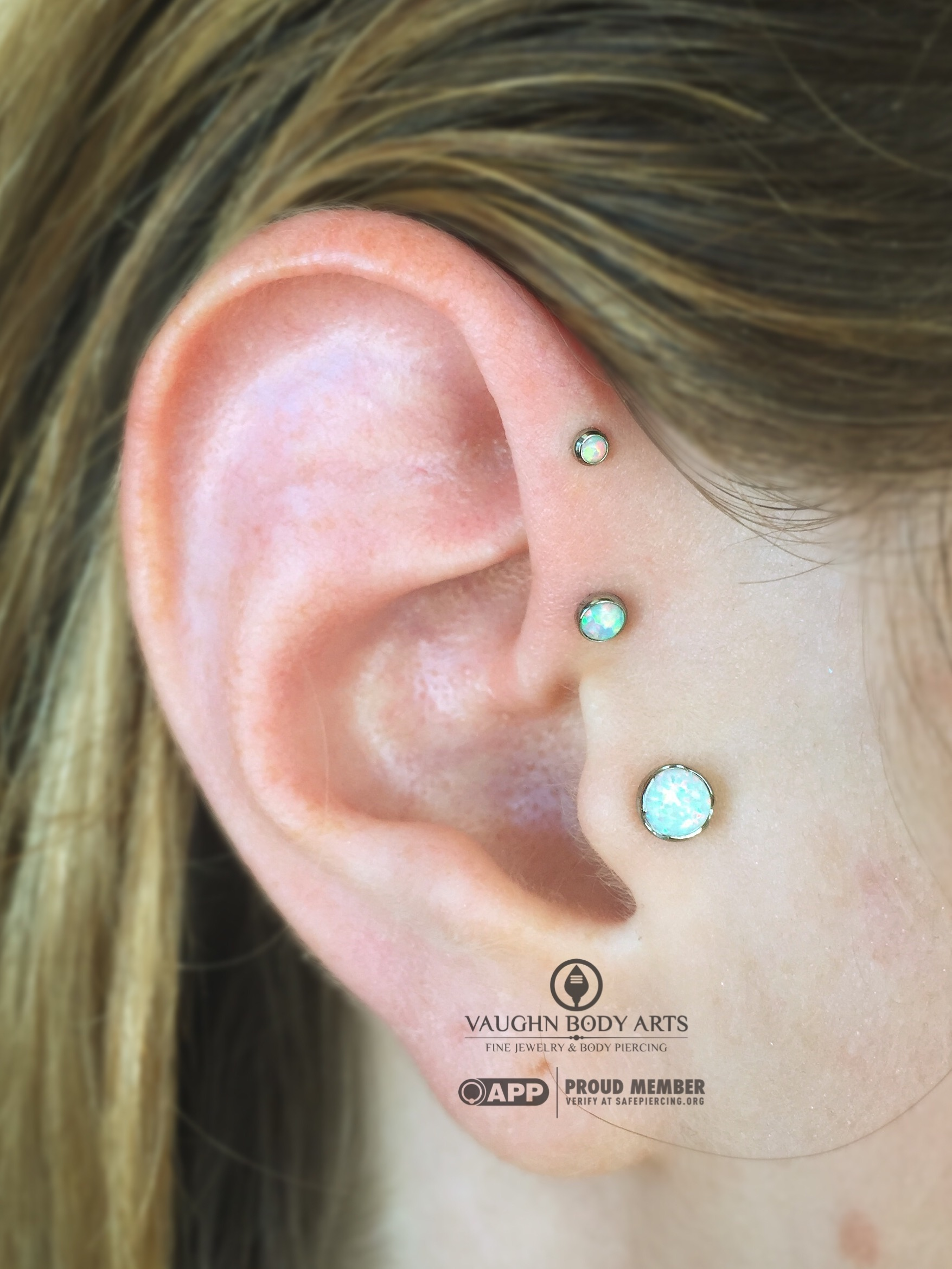 Double forward helix and tragus piercings with titanium jewelry from Anatometal.