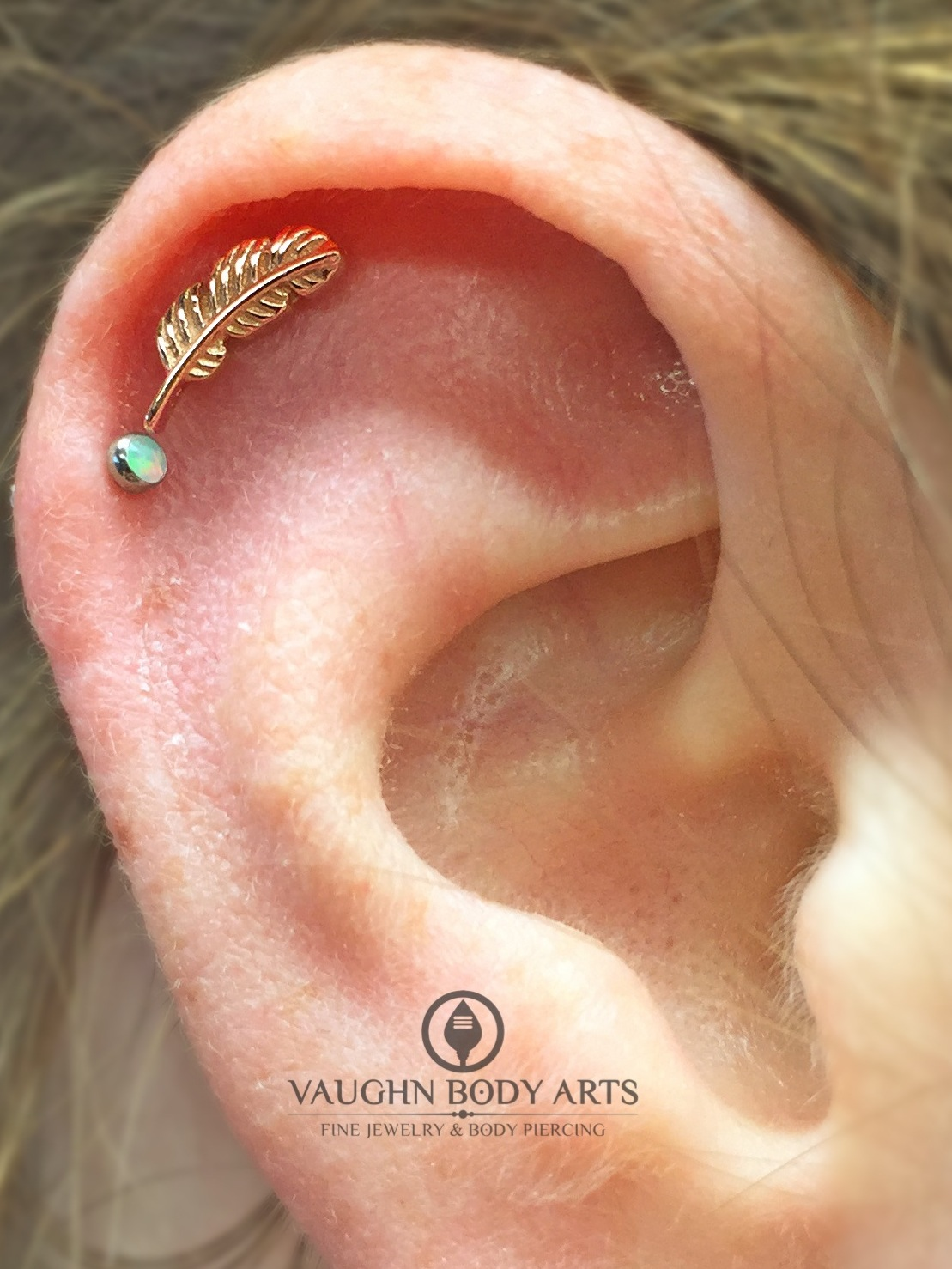 Helix piercing with a 14k rose gold feather end from BVLA.