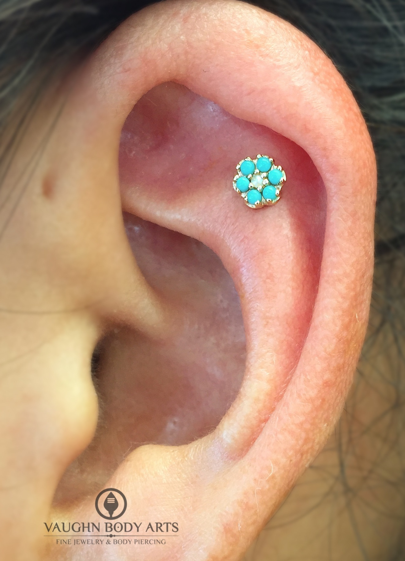 Helix piercing with a 14k yellow flower featuring turquoise and a genuine pearl from BVLA.