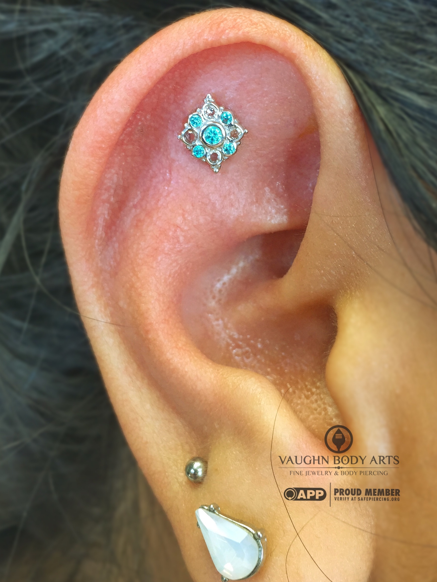 """Helix piercing with a 14k white gold """"Angela"""" end featuring mint green cz's and white sapphires from BVLA."""