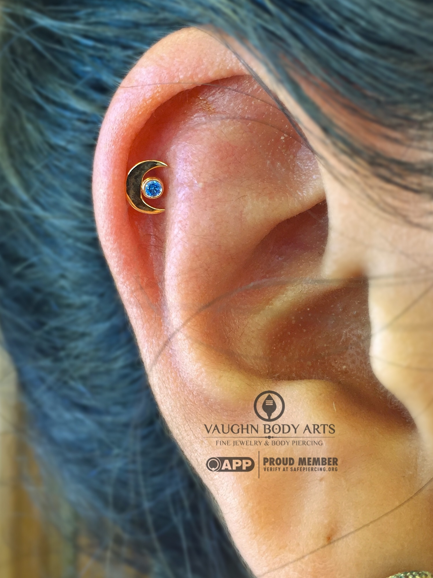 Helix piercing with an 18k yellow gold crescent moon end from Anatometal.