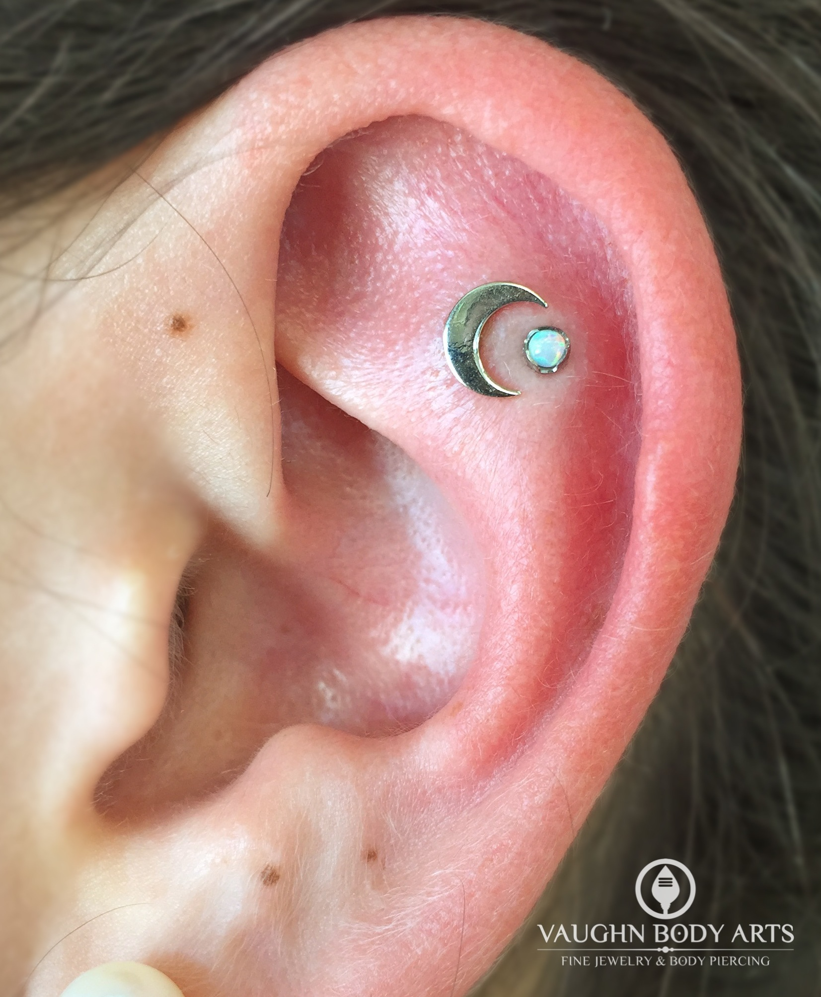 Helix piercings with an 18k white gold crescent moon and titanium jewelry from Anatometal.