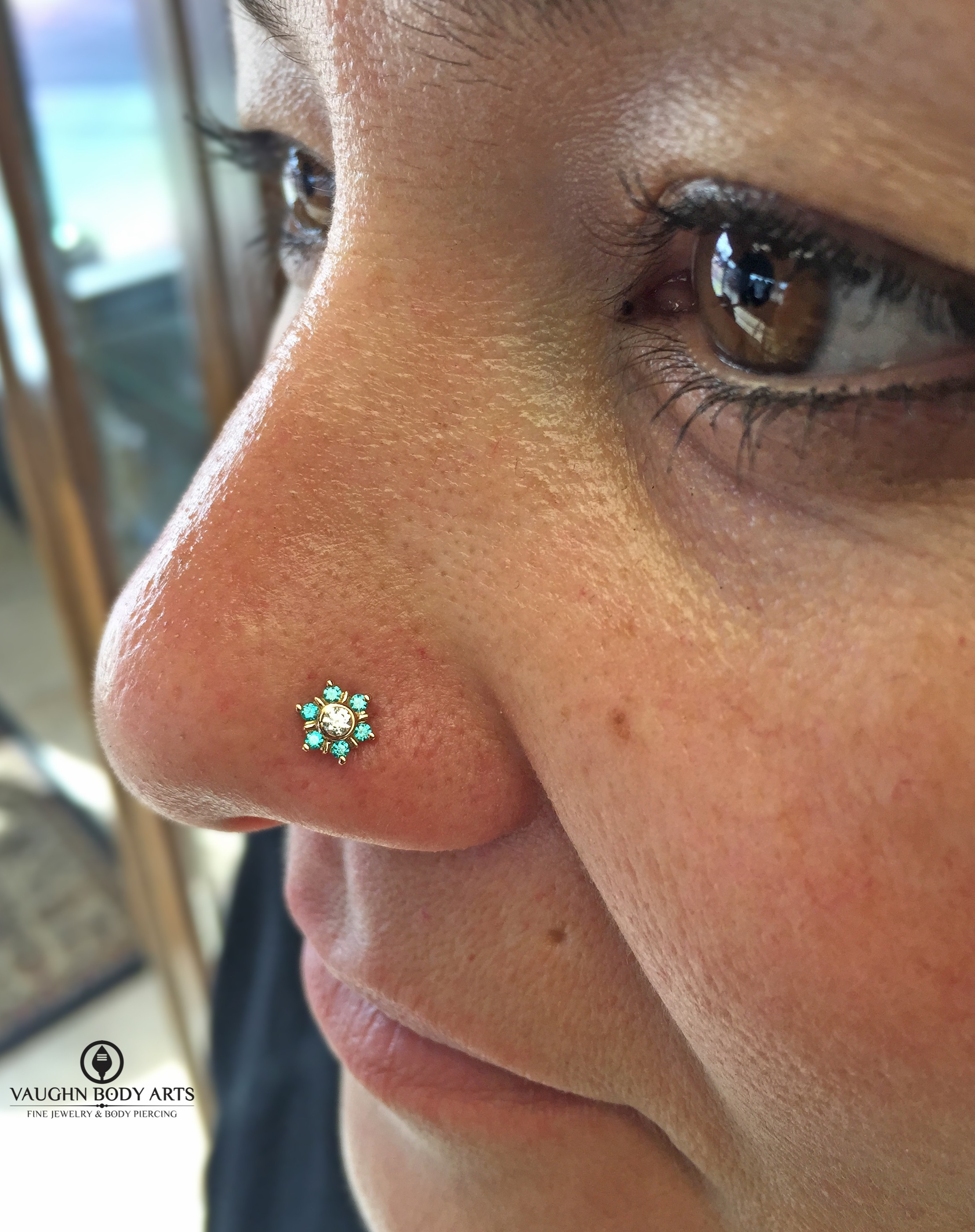 """Nostril piercing (not done by us) upgraded to a 14k yellow gold """"Toltec"""" end featuring mint green and clear cz's from BVLA."""