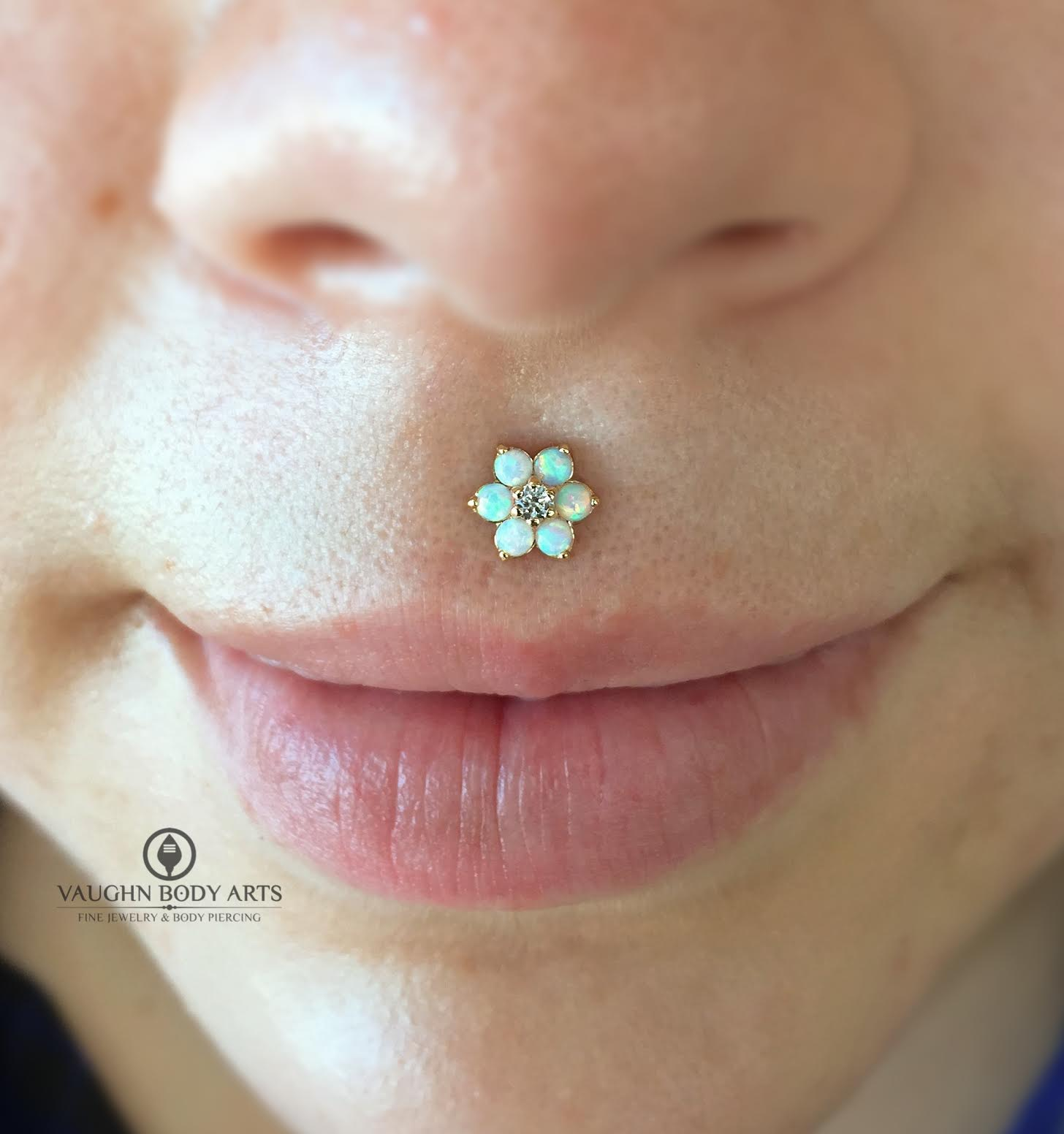 Philtrum piercing with an 18k yellow gold flower from Anatometal.