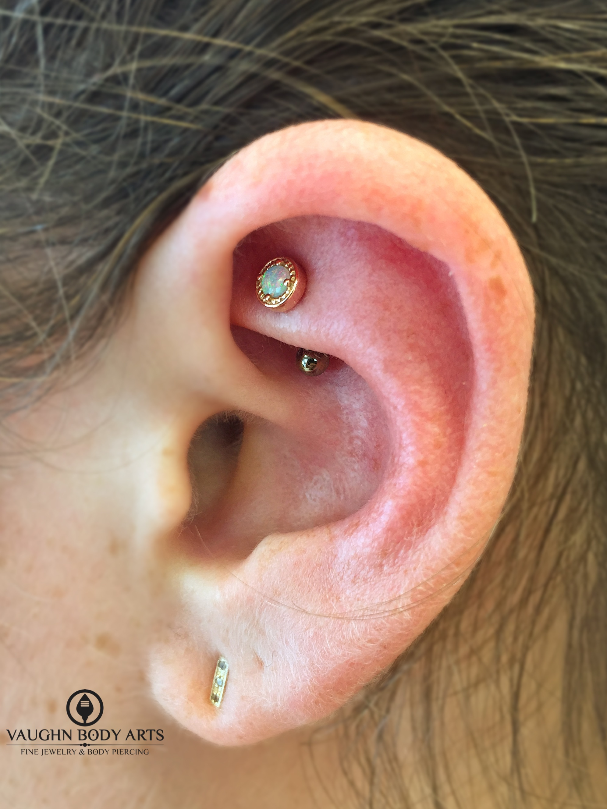 """Rook piercing with a 14k yellow gold and opal """"Millgrain Prong"""" end from BVLA."""