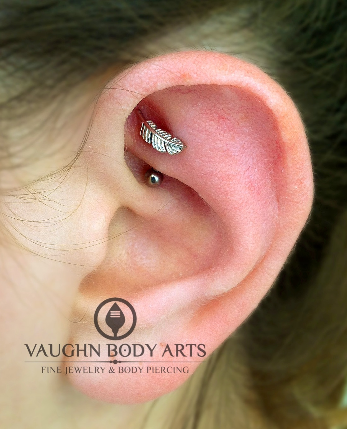 Rook piercing with a 14k white gold feather end from BVLA.
