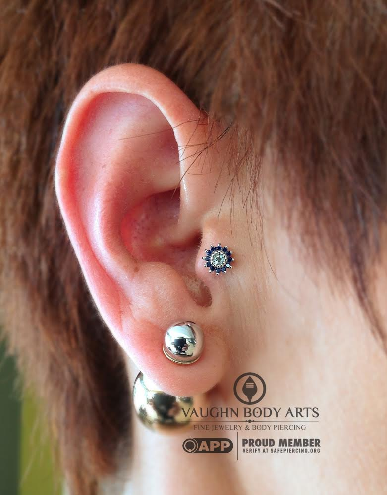 """Tragus piercing with a 14k white gold """"Rose"""" featuring genuine sapphires and aquamarine from BVLA."""