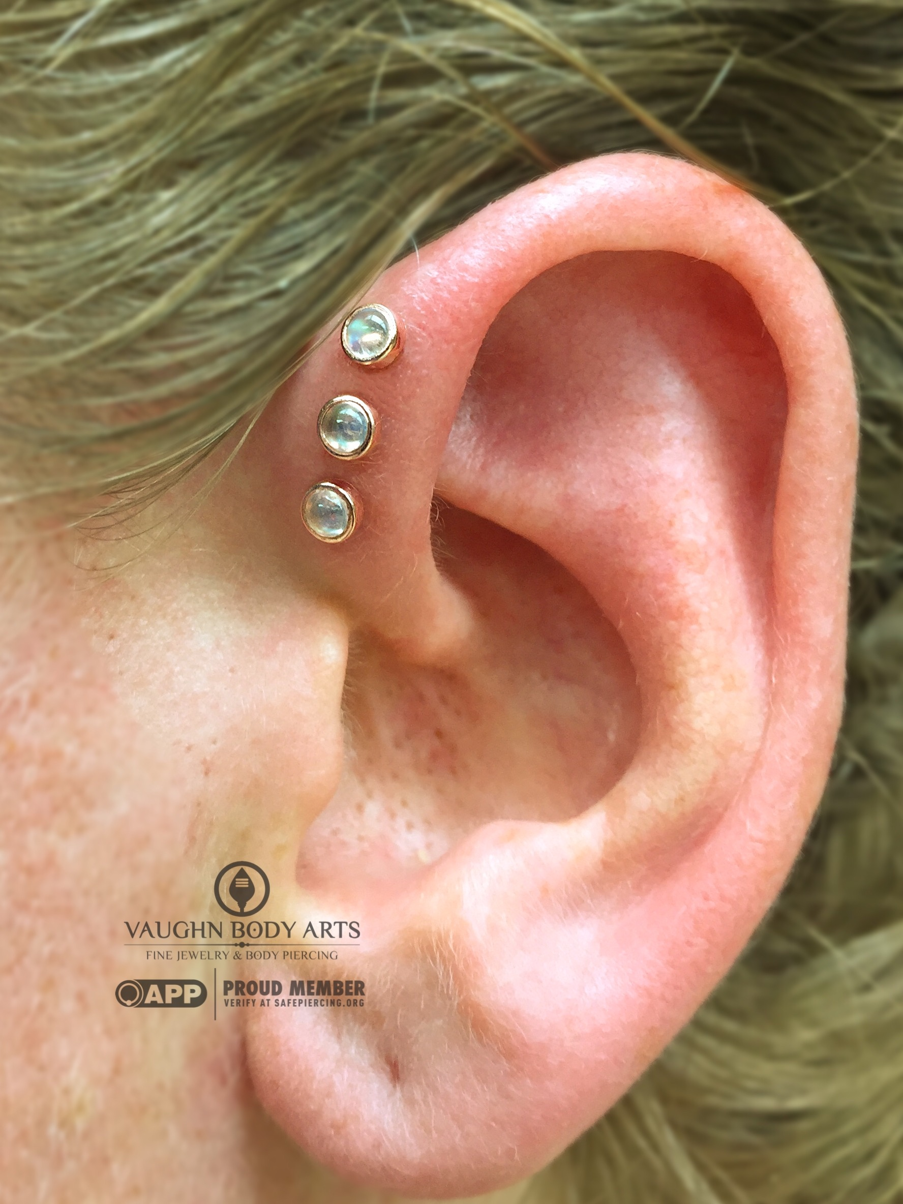 Triple helix piercings featuring 14k rose gold and genuine rainbow moonstone ends from BVLA.