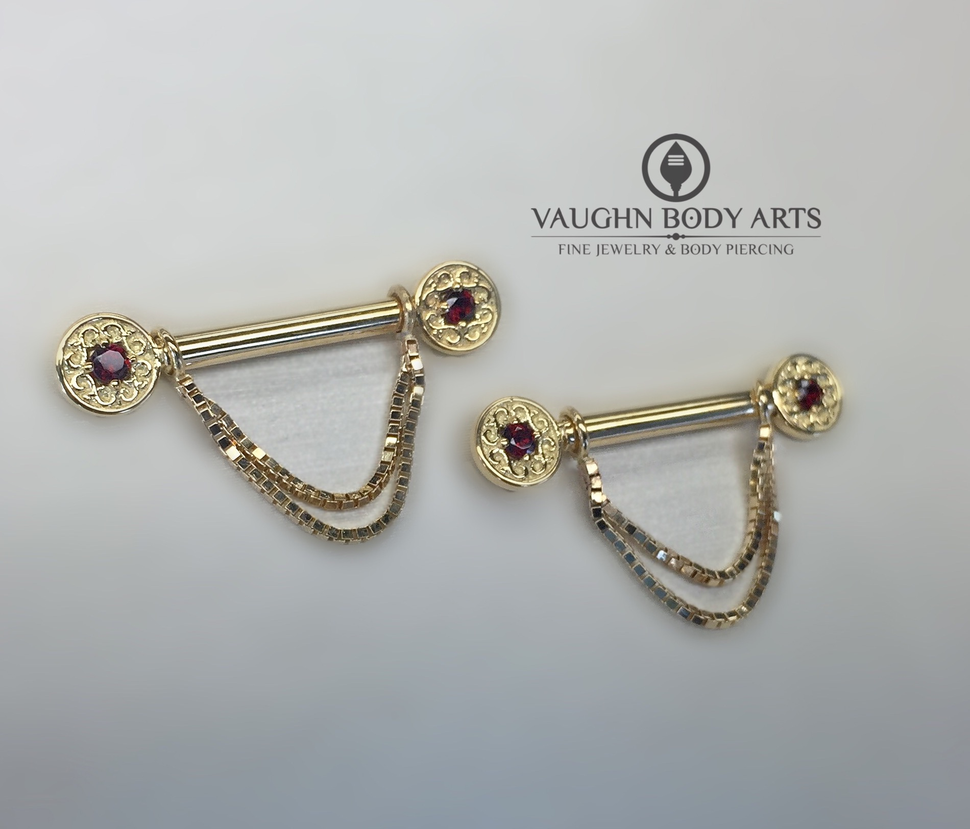 "Custom 18k yellow gold barbells with ""Elizabeth"" ends featuring genuine garnets, and removable box-chains. From BVLA."
