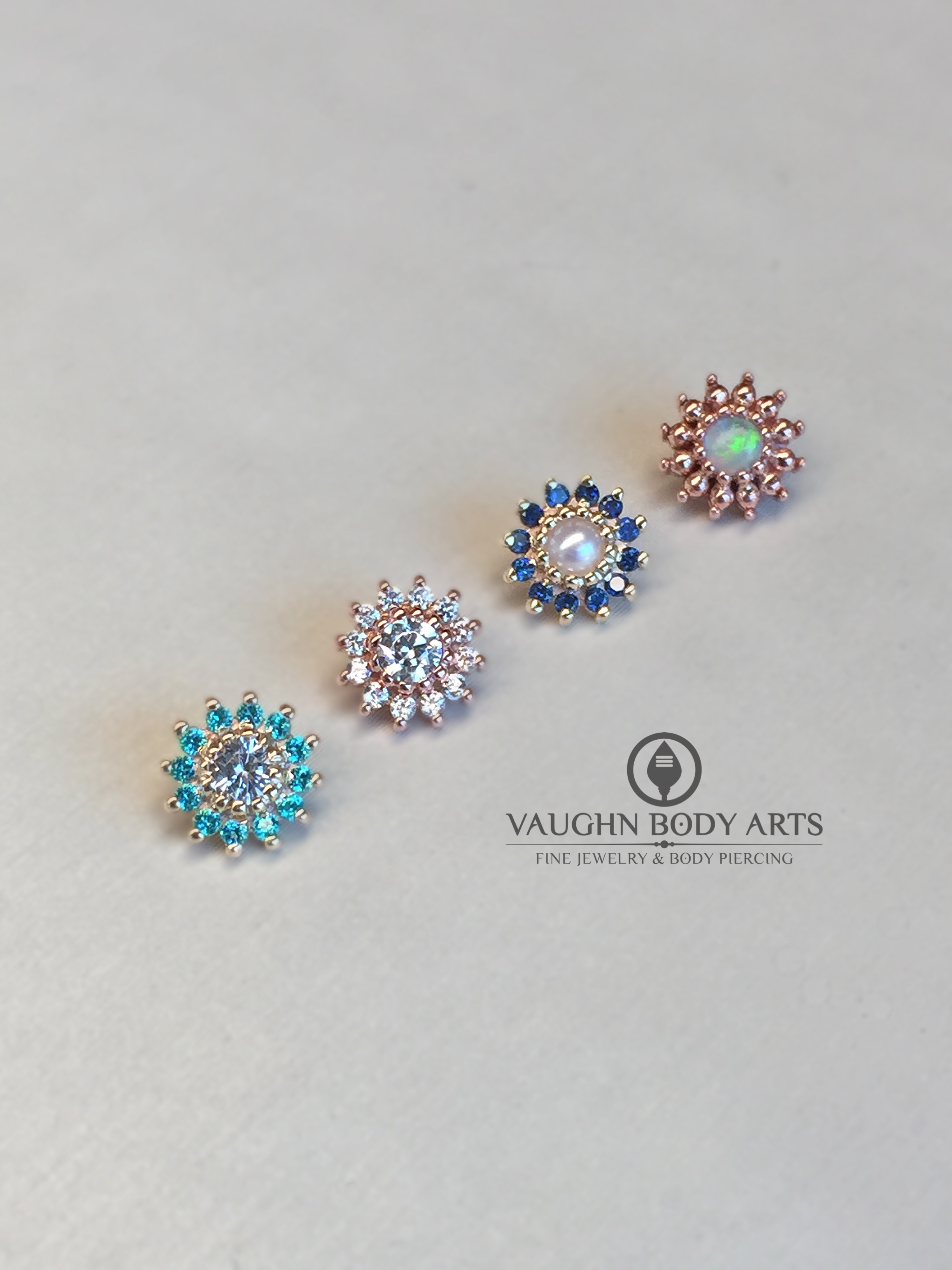 "Selection of 14k gold ""Rose"" ends from BVLA, from left to right:  yellow gold with paraiba and white topaz, rose gold with white sapphires, yellow gold with sapphires and pearl, and rose gold with white opal."