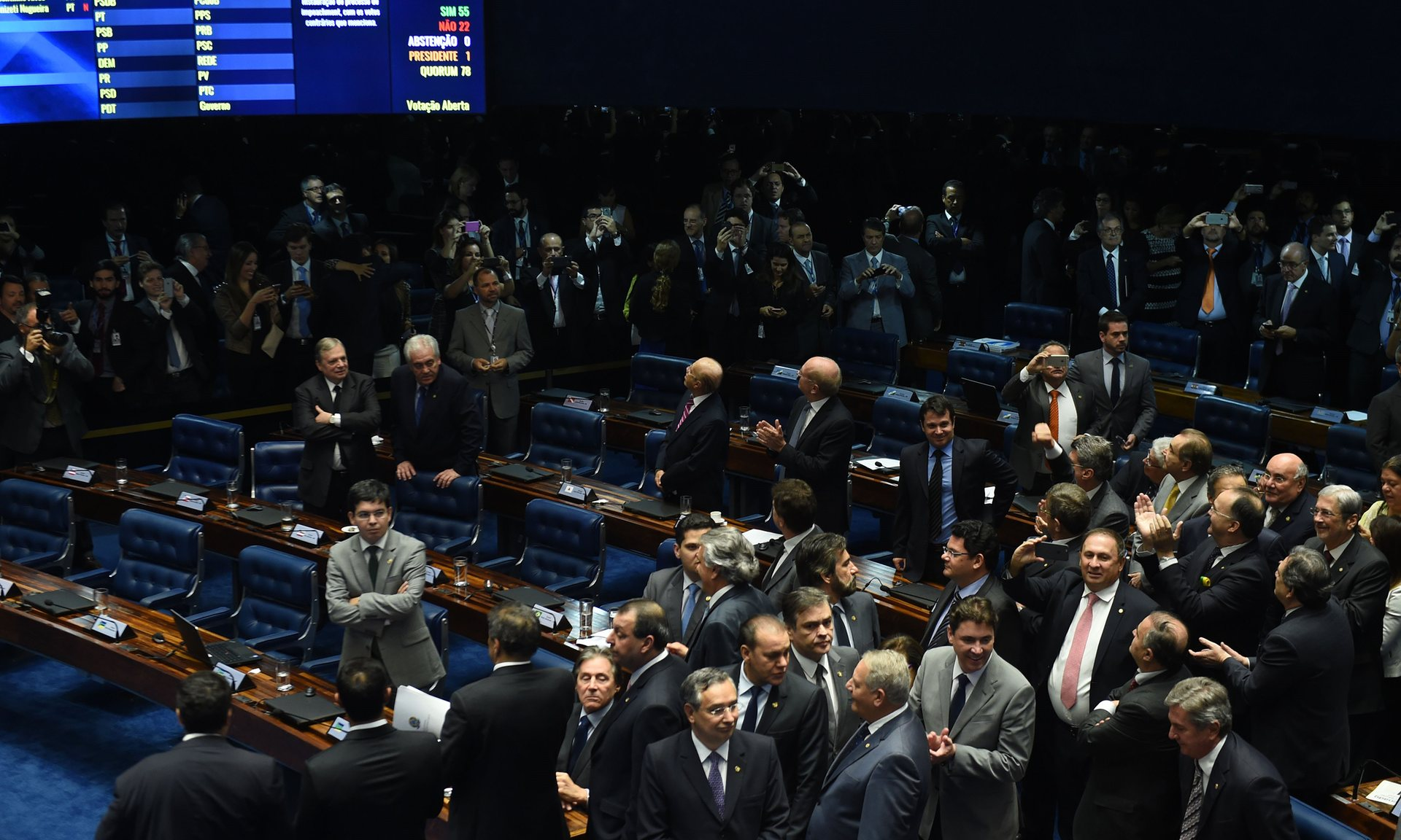 Senators applaud under a large screening displaying the 55-22 vote in favour of impeachment. Source:  The Guardian/Evaristo Sa/AFP/Getty Images
