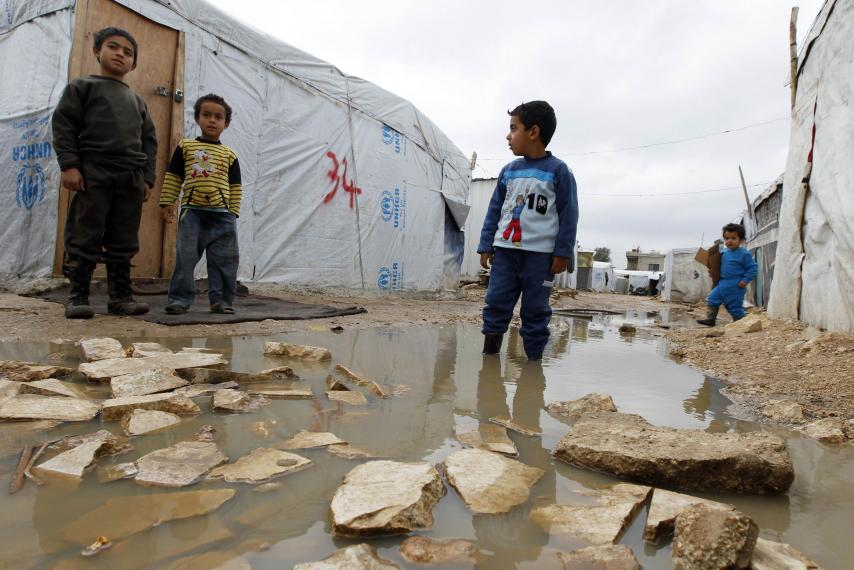 A Syrian refugee boy stands in a pool of water as he looks at others outside tents at a makeshift settlement in Bar Elias in Lebanon's Bekaa Valley, January 5, 2015. Source:  newsweek.com