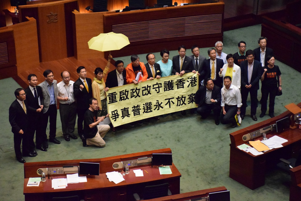 20 Pro-Democratic Lawmakers protest in LegCo in favor of true democracy after a Beijing reform package was rejected in the summer of 2015. Source: Wikimedia commons