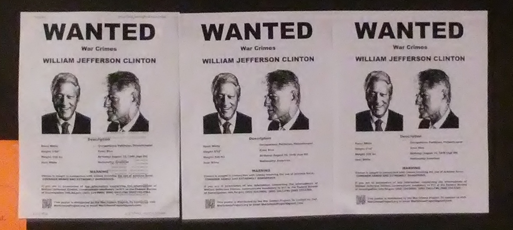 Wanted posters hanging in a hallway.