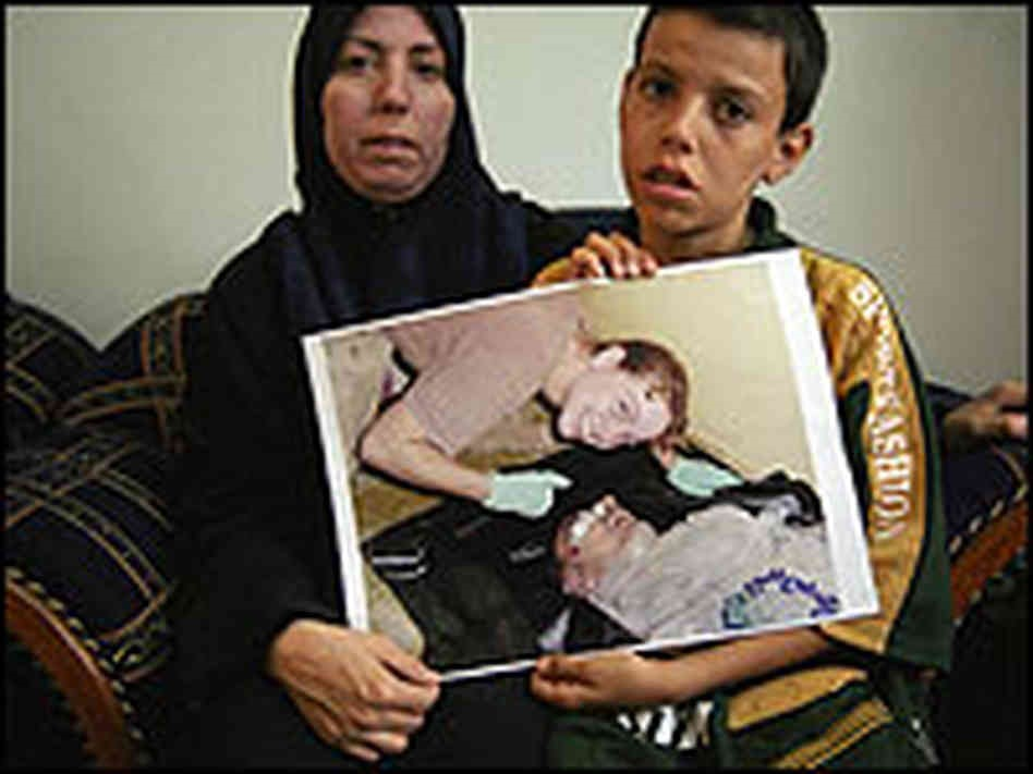 Manadel al-Jamadi's wife and son hold a picture of US Army Military Police Officer Sabrina Harman smiling over Manadel's dead body. Harman was sentenced to only six months in prison for her role in the sexual, physical, and psychological abuse of prisoners, including Manadel.