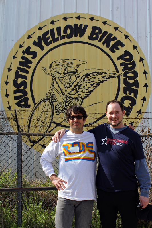 RST CEO Aaron Rippenkroeger (right) and Patrick Jones, who helped coordinate the RIde, pose in front of the Yellow Bike Project.