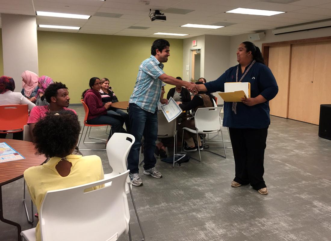 Virginia hands a graduation certificate to an ESL student