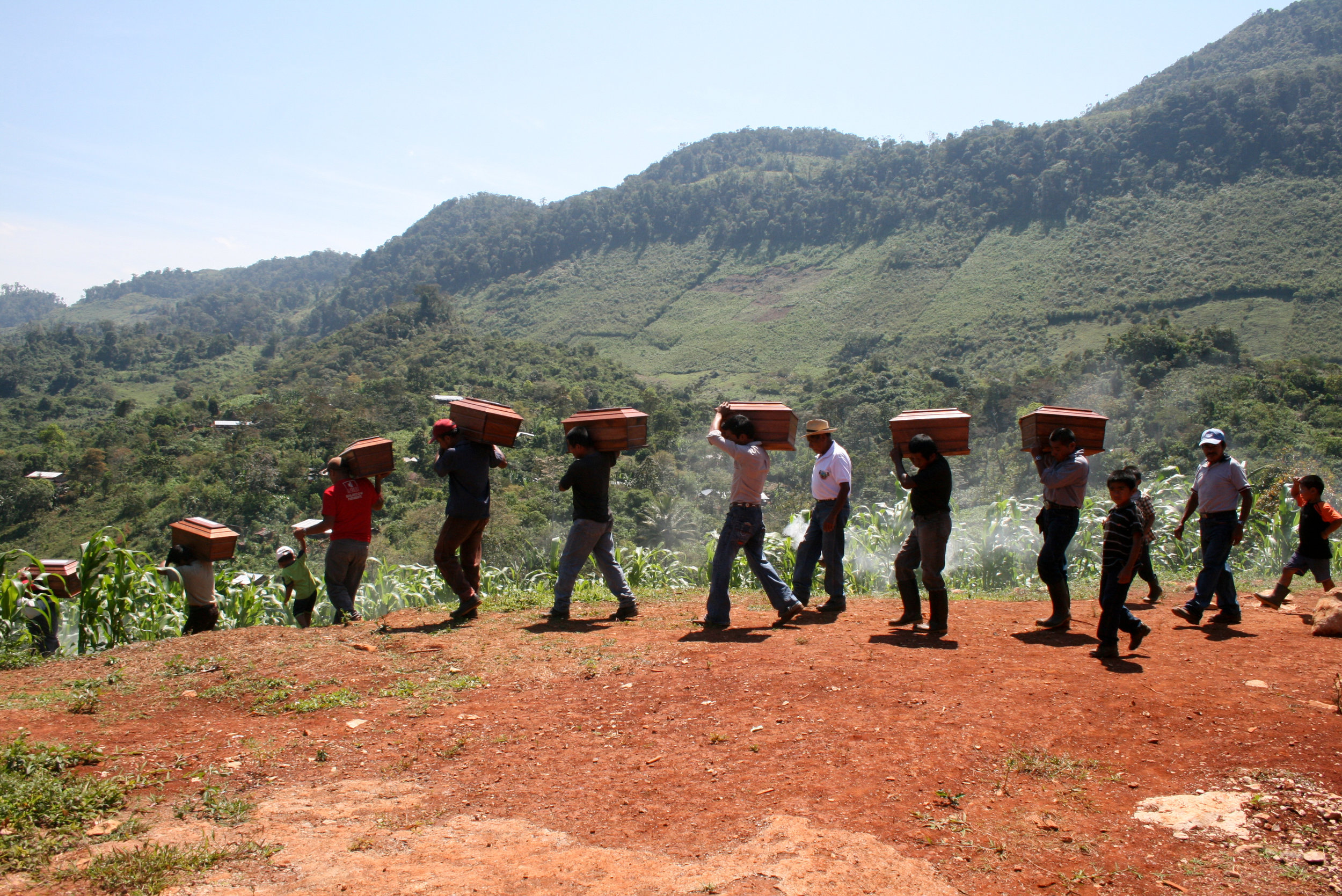 Ixil people carrying their loved ones' remains after an exhumation in the Ixil Triangle in February 2012.