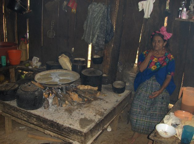 """The villagers traditionally cook on open """"three stone"""" fires. They use these fires to boil water, cook, and heat their huts."""