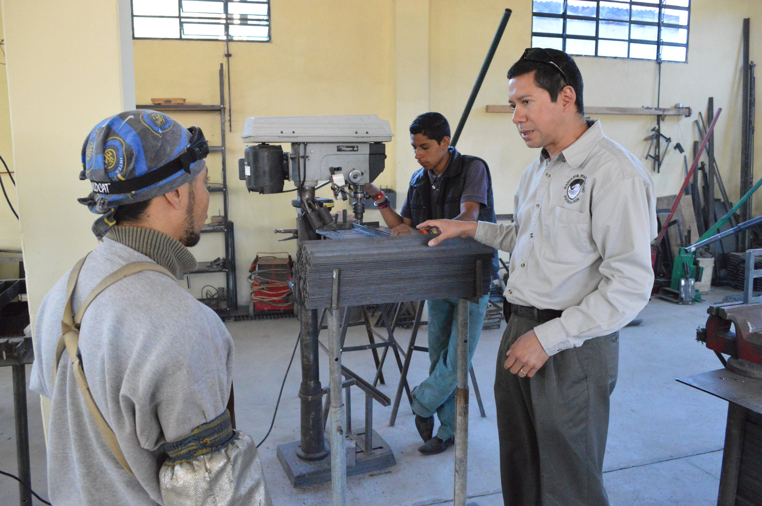 Marco Tulio Maldonado, Guatemala Field Director, talking with a worker at the Aller Skill Center.