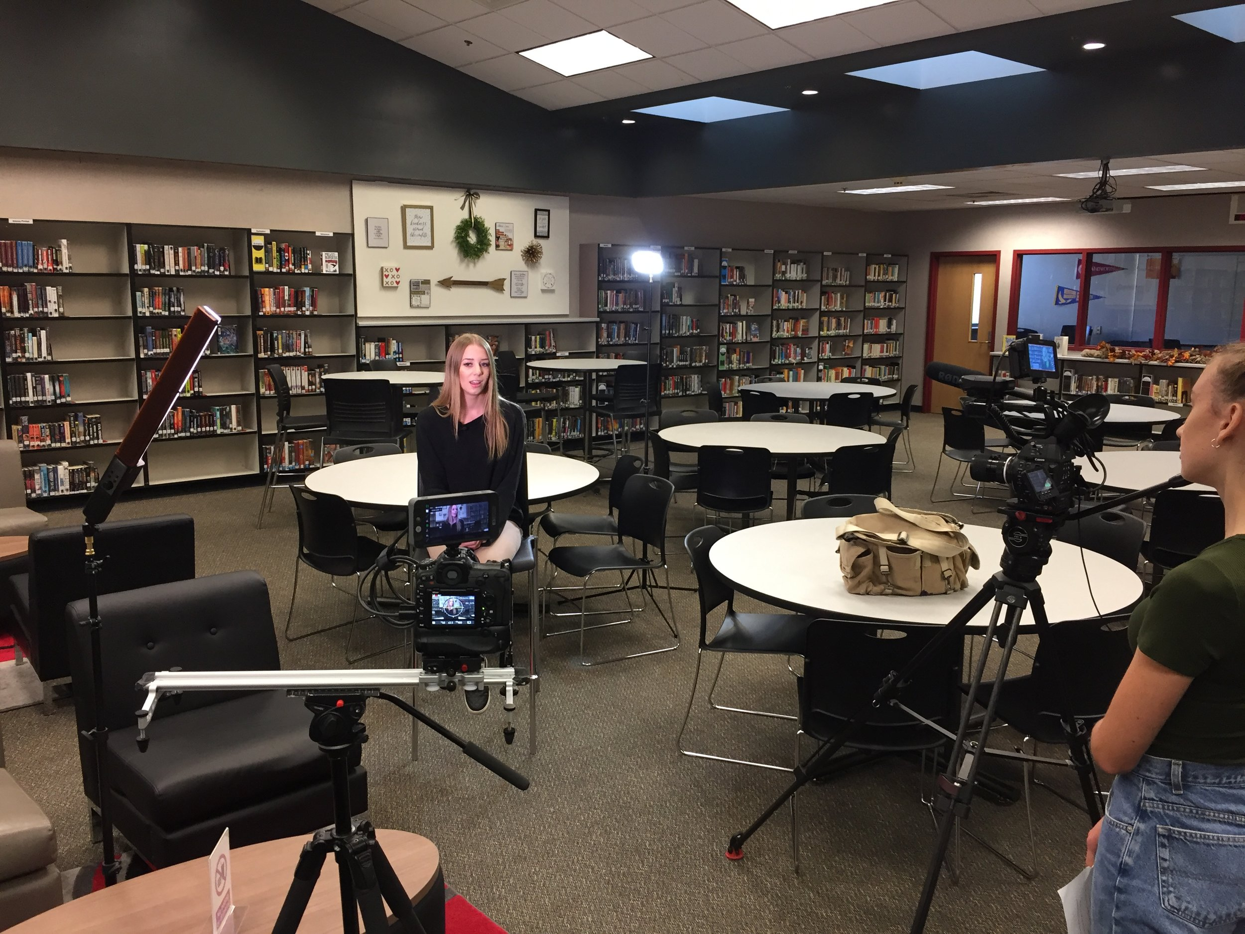 Interview inside the library. Taylor (left) asks questions while Andie (behind Taylor) operates the camera.