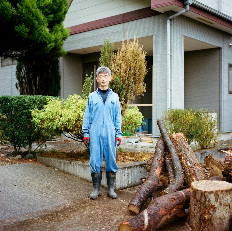 Cet homme travaille à la centrale Fukushima Daini, à quelques kilomètres au nord de Naraha, à la limite de l'actuelle zone d'évacuation. Cette centrale a beaucoup moins souffert du tsunami que celle de Fukushima Daiichi, mais elle reste néanmoins à l'arrêt. Il souhaite revenir vivre dans sa maison; sa femme et ses enfants aussi. Il me raconte que le gouvernement est venu décontaminer sa maison en lavant simplement les murs et le toit.Les bûches à côté de lui sont pour sa cheminée. Il vient de réparer sa salle de bain et il reste de temps en temps les week-ends dans la maison.