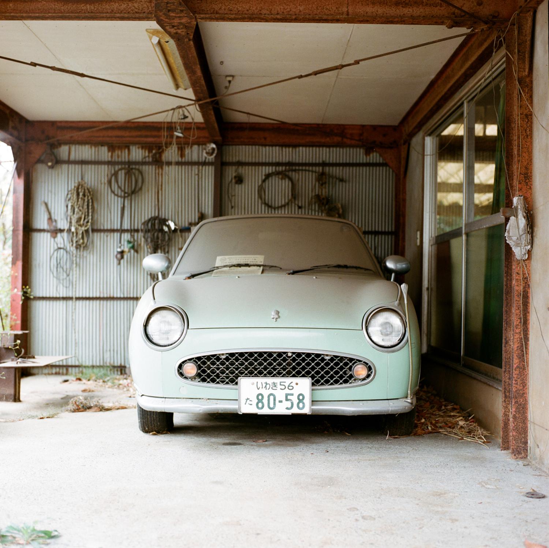Une Nissan Figaro, voiture de collection construite à 20 000 exemplaires à la fin des années 1980. Elle prend la poussière depuis plus de quatre ans et attend le retour de son propriétaire.