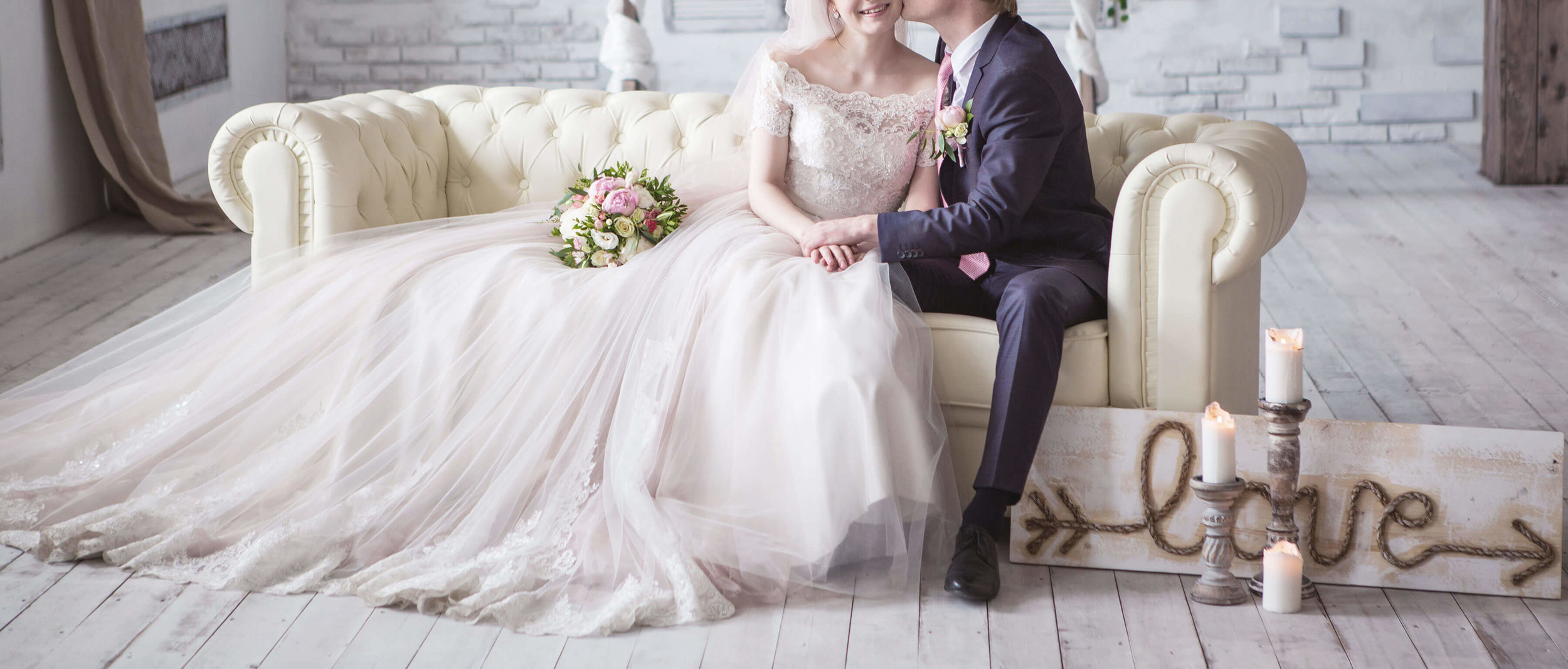 bride and groom sitting on white couch