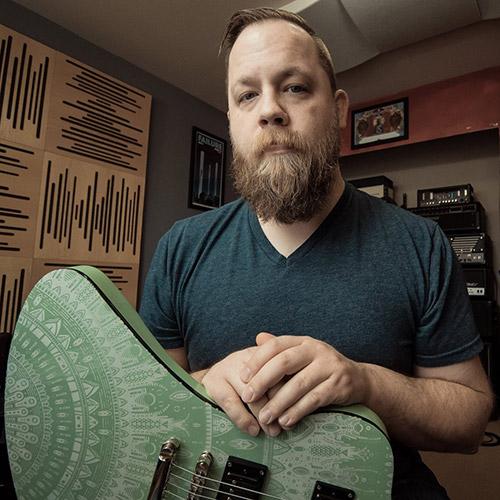 Testimonials Ryan Fluff Bruce holding his custom laser etched burntaxe Mandala one signature Balaguer guitar