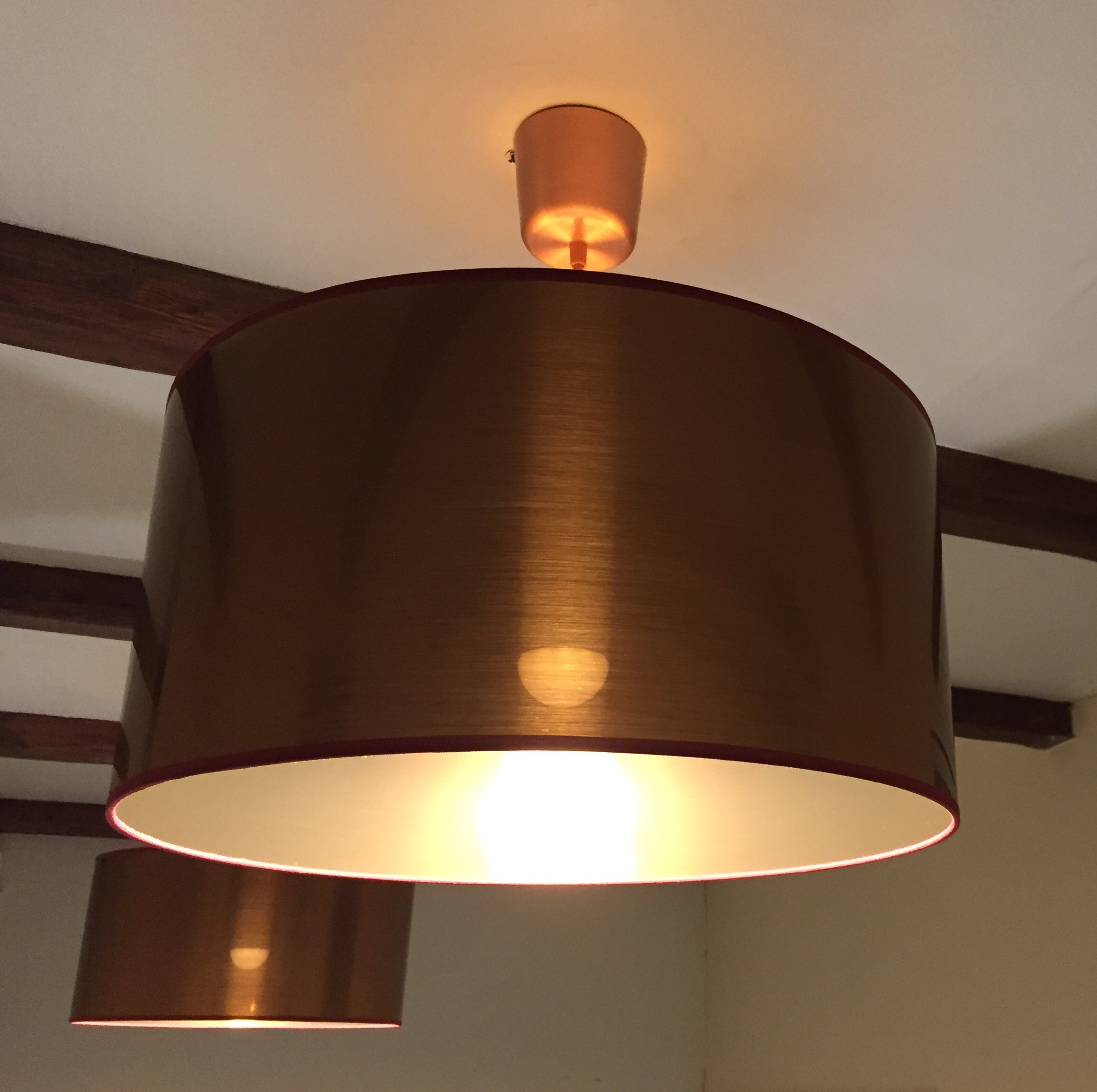 These copper drum shades bring an element of industrial chic to this room.  Specified and installed by the electrical contractor when the client wanted something more than the high street could offer and paired with an energy efficient LED light source to provide upward illumination onto the beamed ceiling feature.