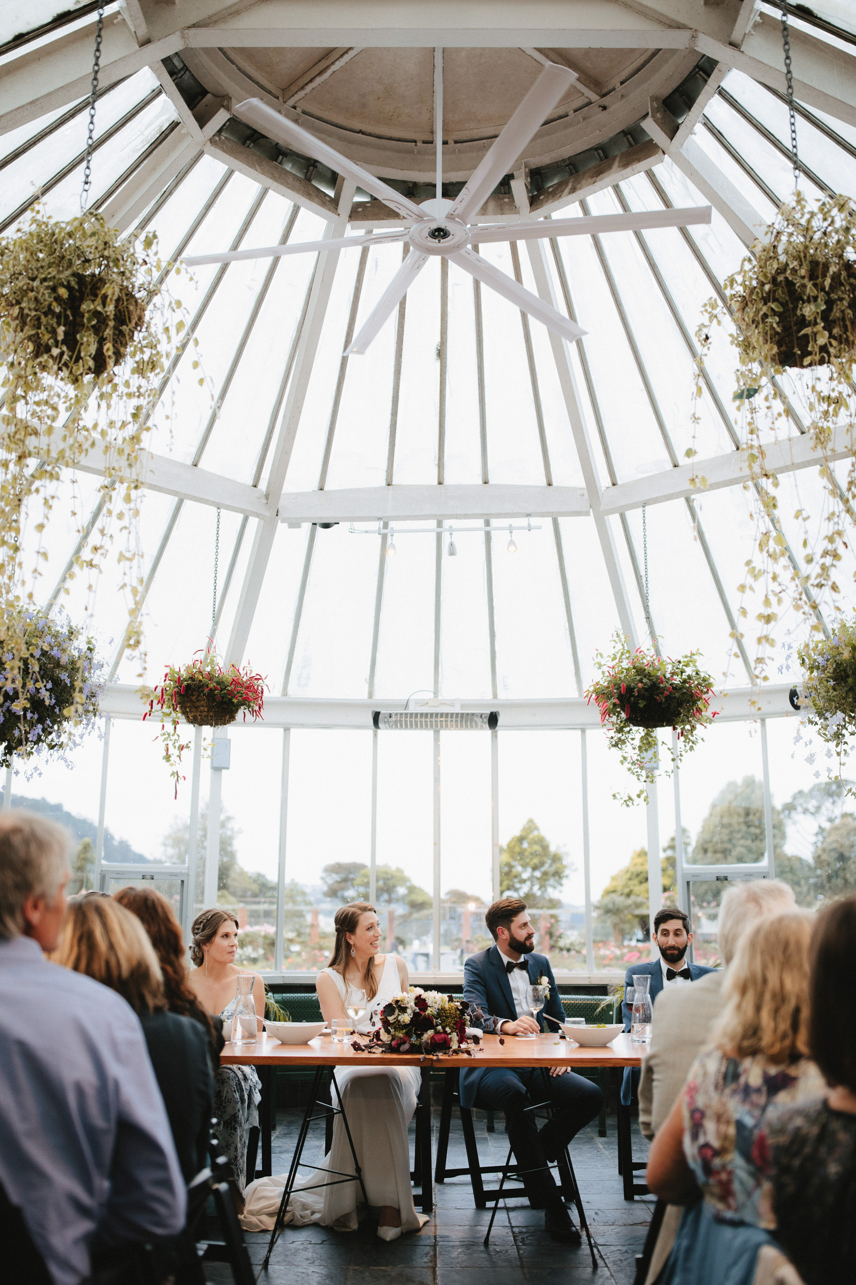 Bride and Groom listen to speeches at their glasshouse wedding reception