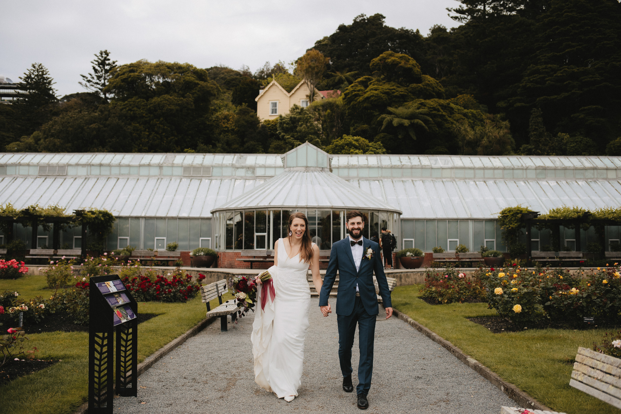 Their glasshouse wedding reception parties on behind them at the Botanic Gardens in Wellington