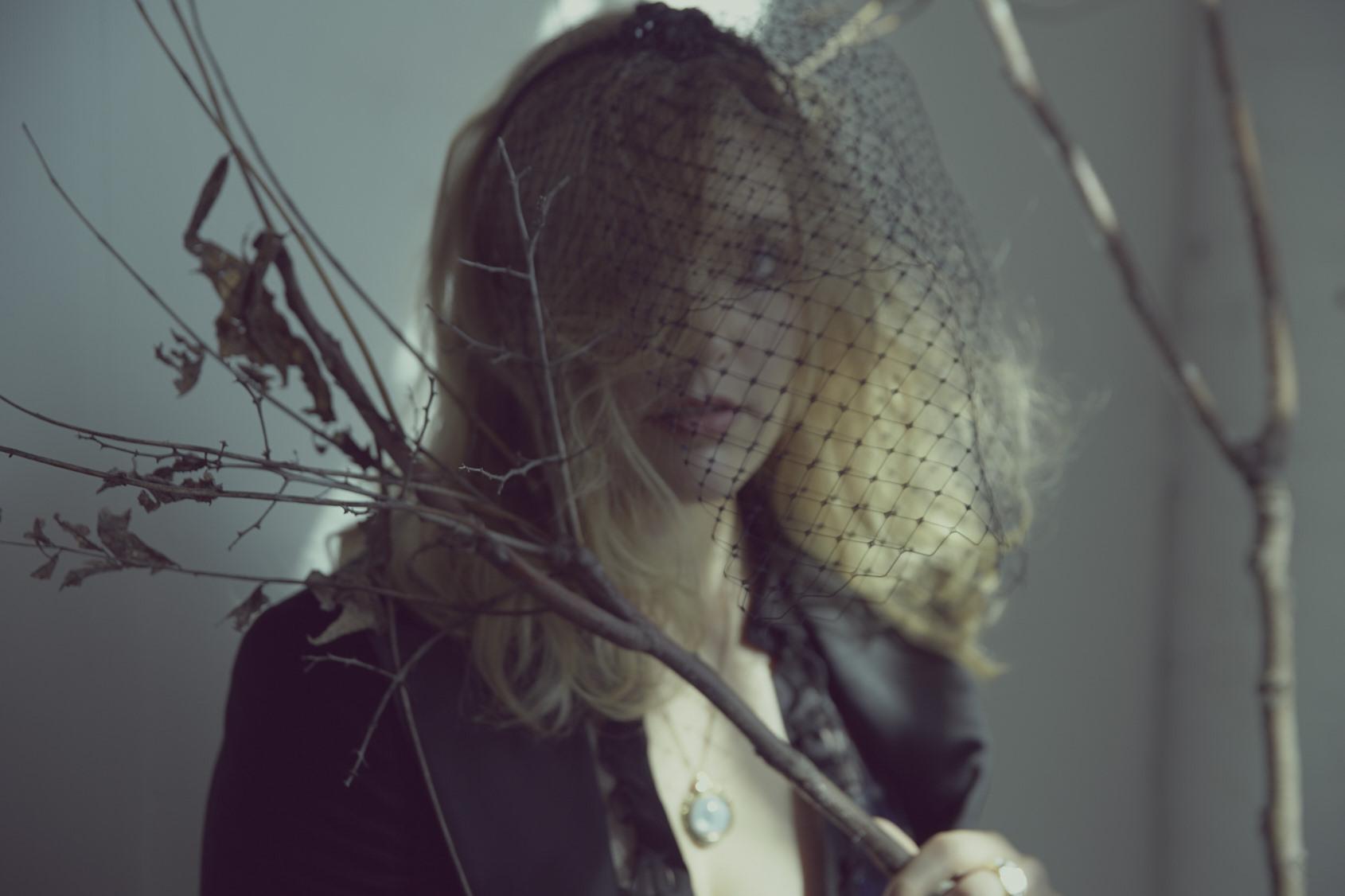 Blazer by Pierre Balmain, blouse by Saint Laurent, veil by Maison Michel, necklace by Pamela Love