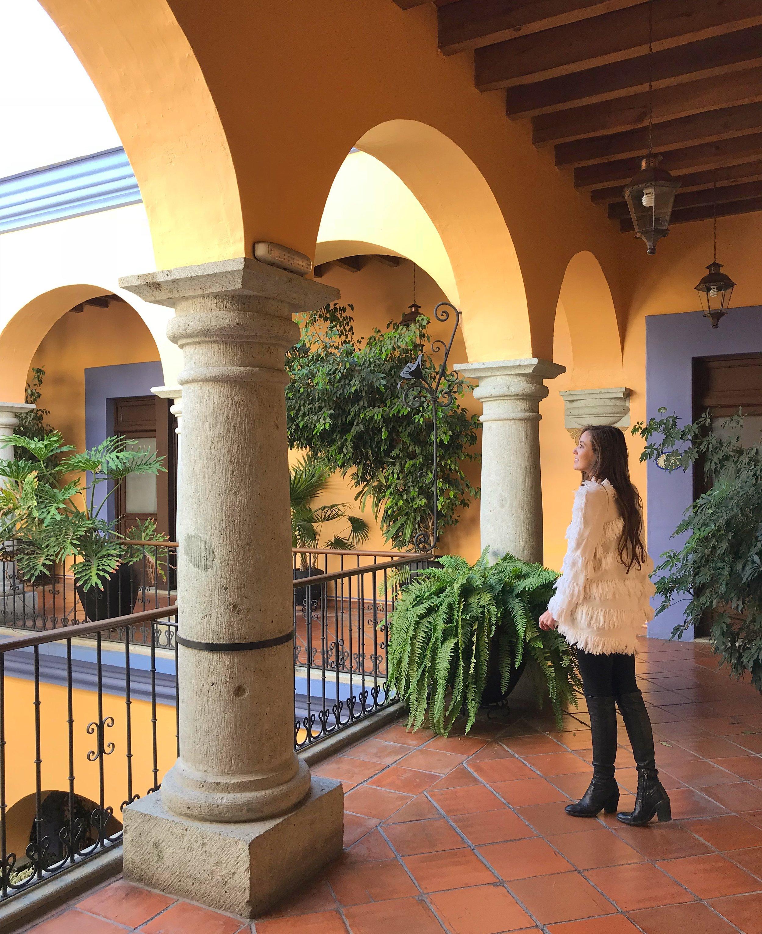 carina otero in the colorful corridors of hostal de la noria, oaxaca