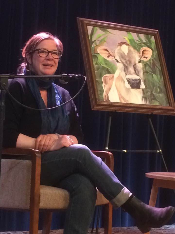 me speaking, with a glamorous painting of a cow for company on stage!