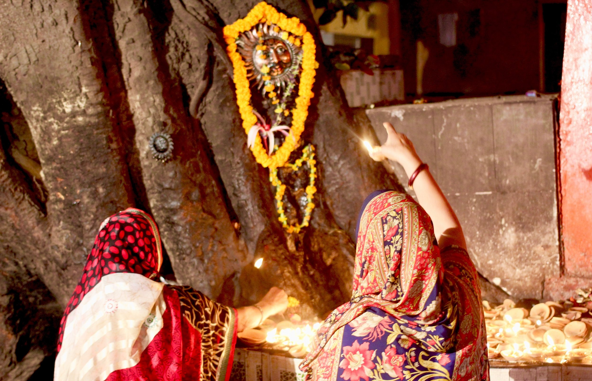 Women making puja (prayer) at a makeshift altar adorned with candles lit inside tiny ceramic bowls.